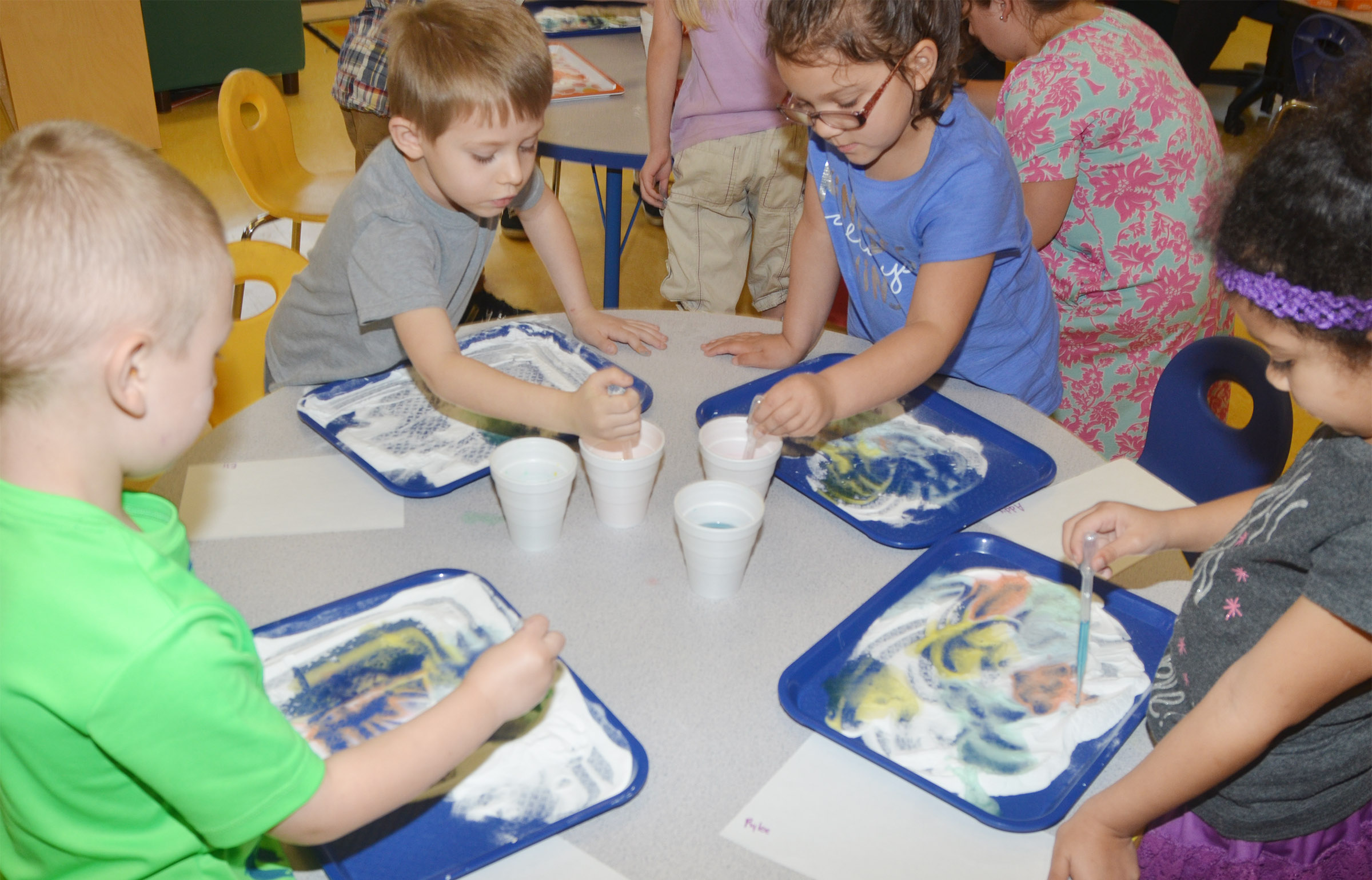 CES preschool students, from left, Cameron Dean, Elijah Russell, Addisyn Taylor and Rylee Karr add colored vinegar to baking soda to see its reaction.