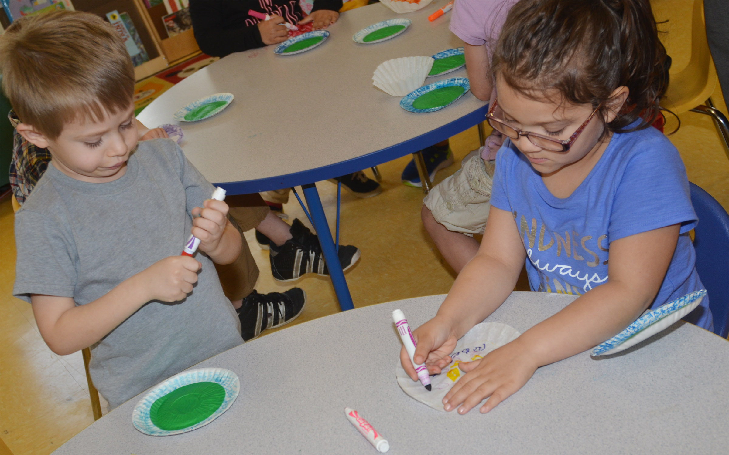 CES preschool students Elijah Russell, at left, and Addisyn Taylor color their coffee filters, which they will use to add a finishing touch to their lily pads.