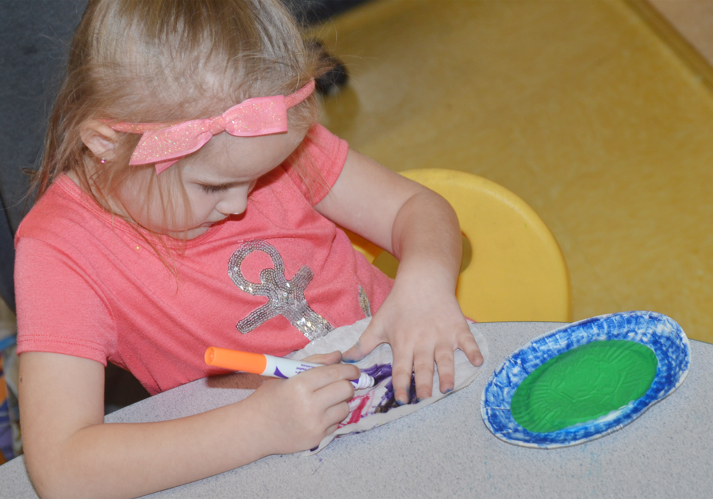 CES preschool student Trinity Dye colors her coffee filter, which will add the finishing touch to her lily pad.