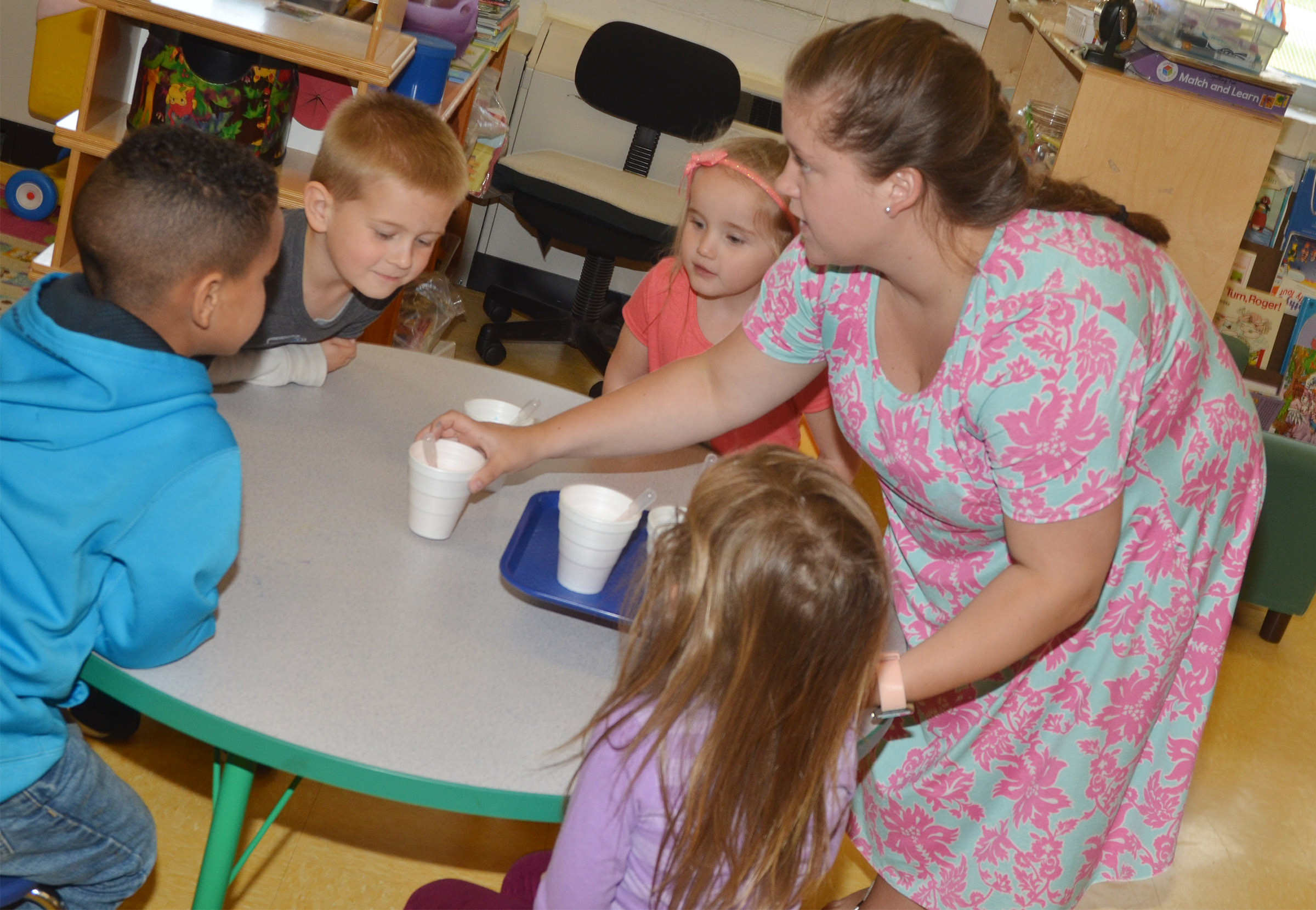 Campbellsville University education student Jordan Bray gives preschool students cups of colored vinegar. They will use the vinegar to see how it reacts with baking soda.