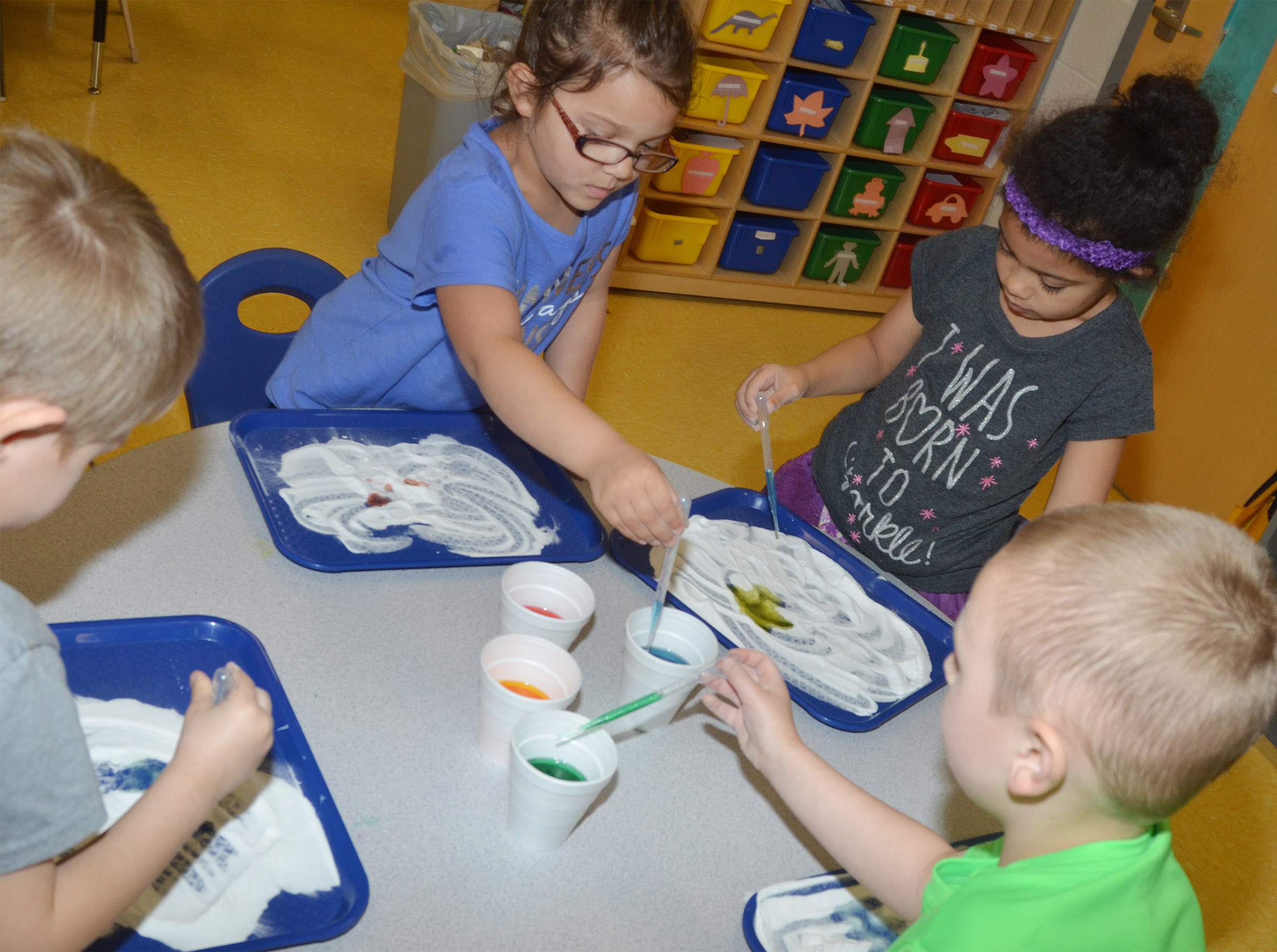 CES preschool students, from left, Elijah Russell, Addisyn Taylor, Rylee Karr and Cameron Dean add colored vinegar to baking soda to see its reaction.
