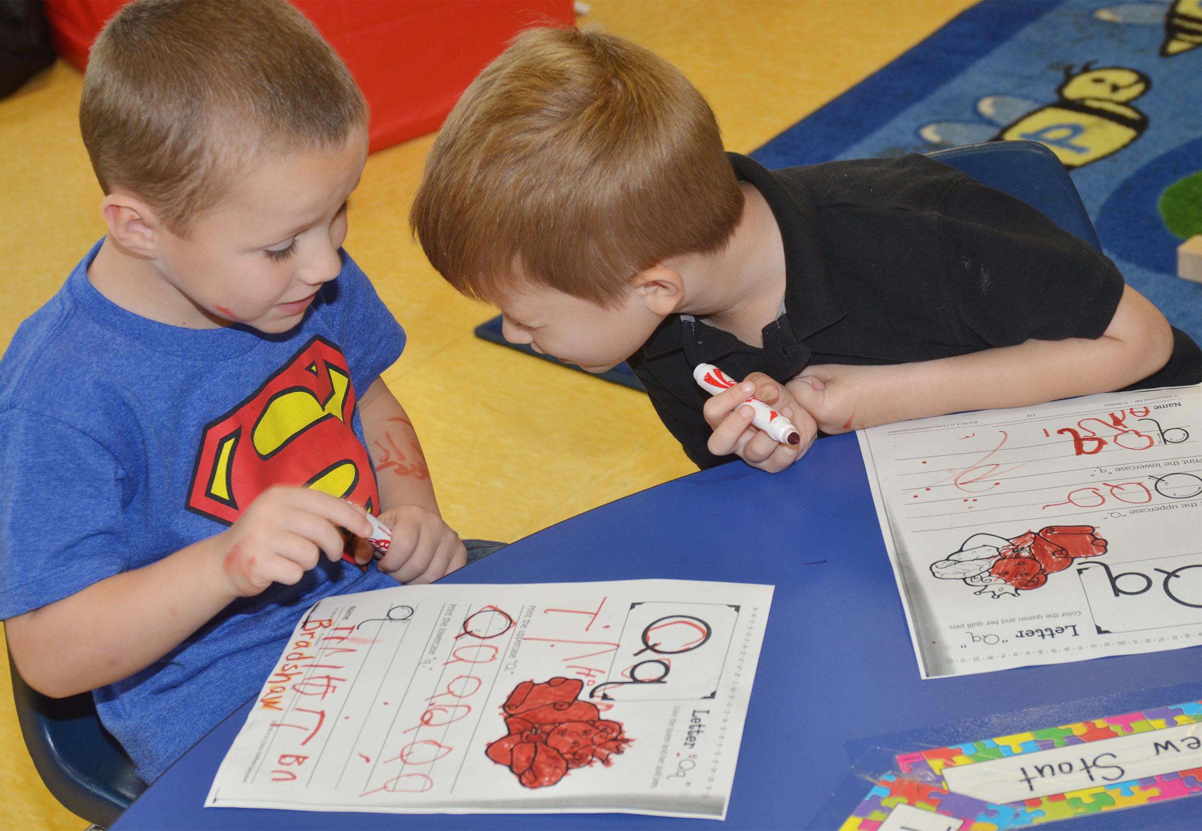 CES preschool students Triton Bradshaw, at left, and Andrew Stout talk as they practice writing the letter Q.