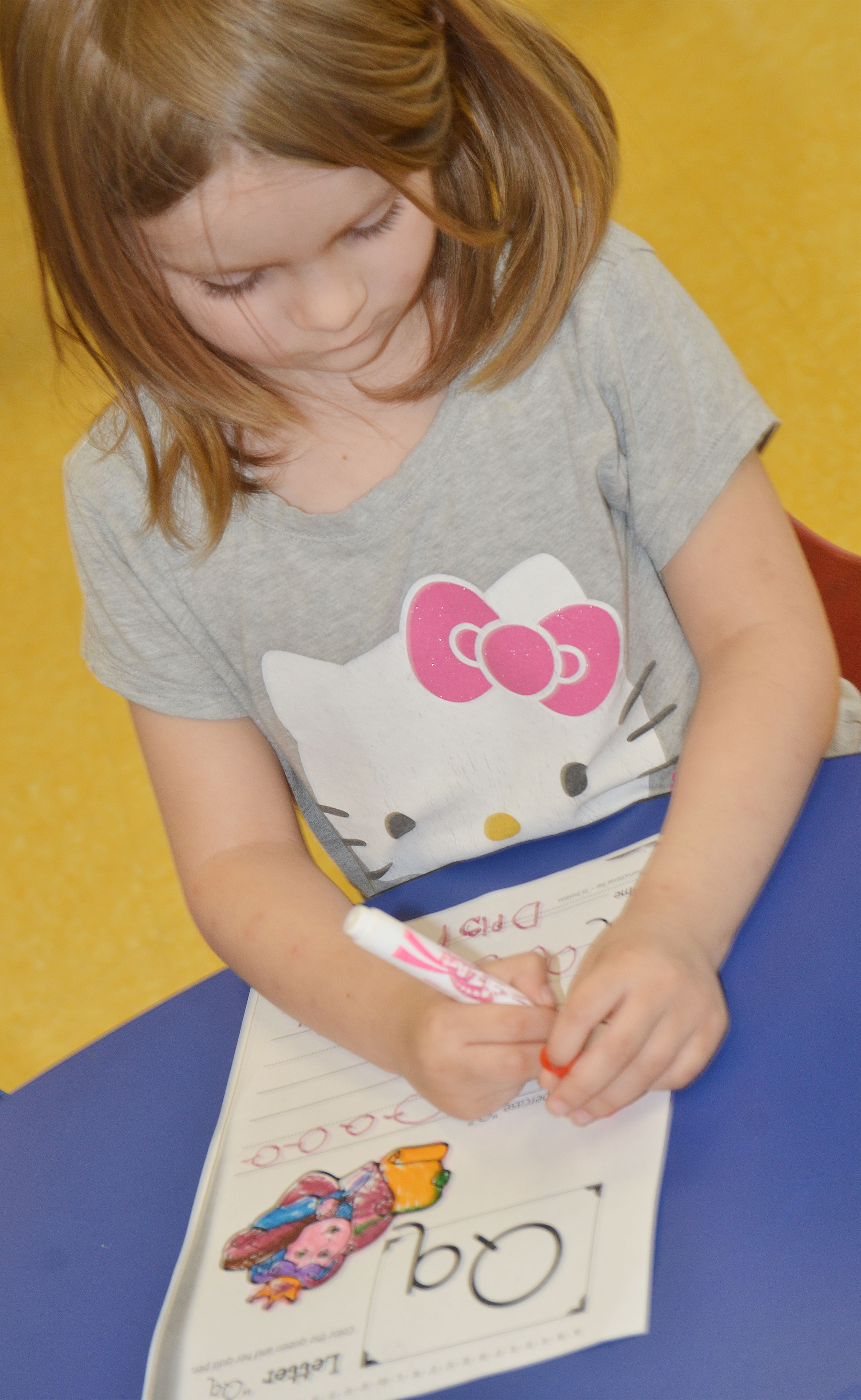 CES preschool student Daisy Rakes writes the letter Q.