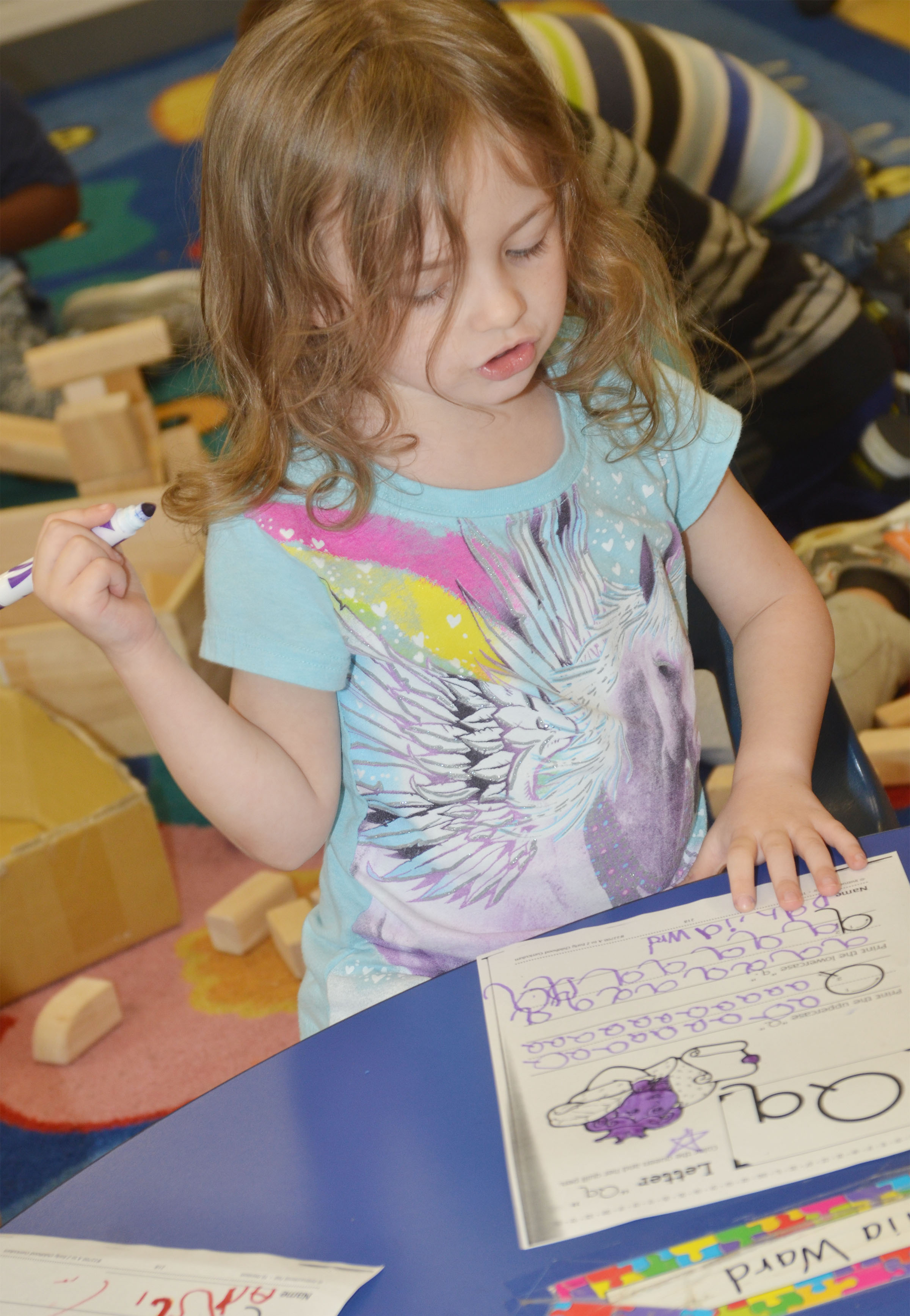 CES preschool student Dahlia Ward writes the letter Q with her favorite color – purple.