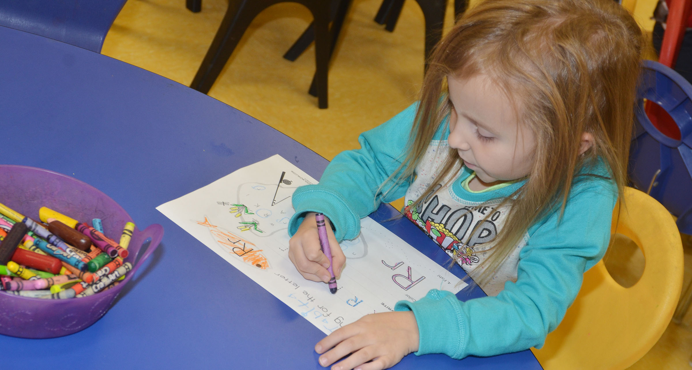 CES preschool student Tabitha Leggett practices writing a lowercase R.