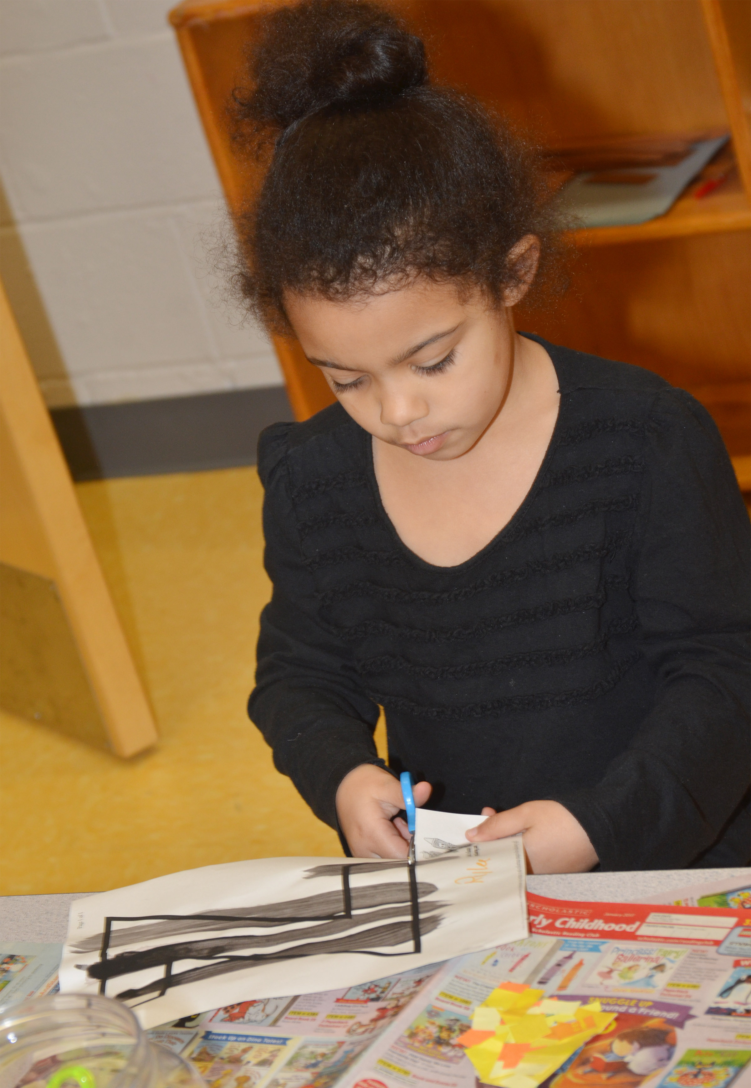 CES preschool student Rylee Karr cuts out her letter Z, which she striped with black paint.