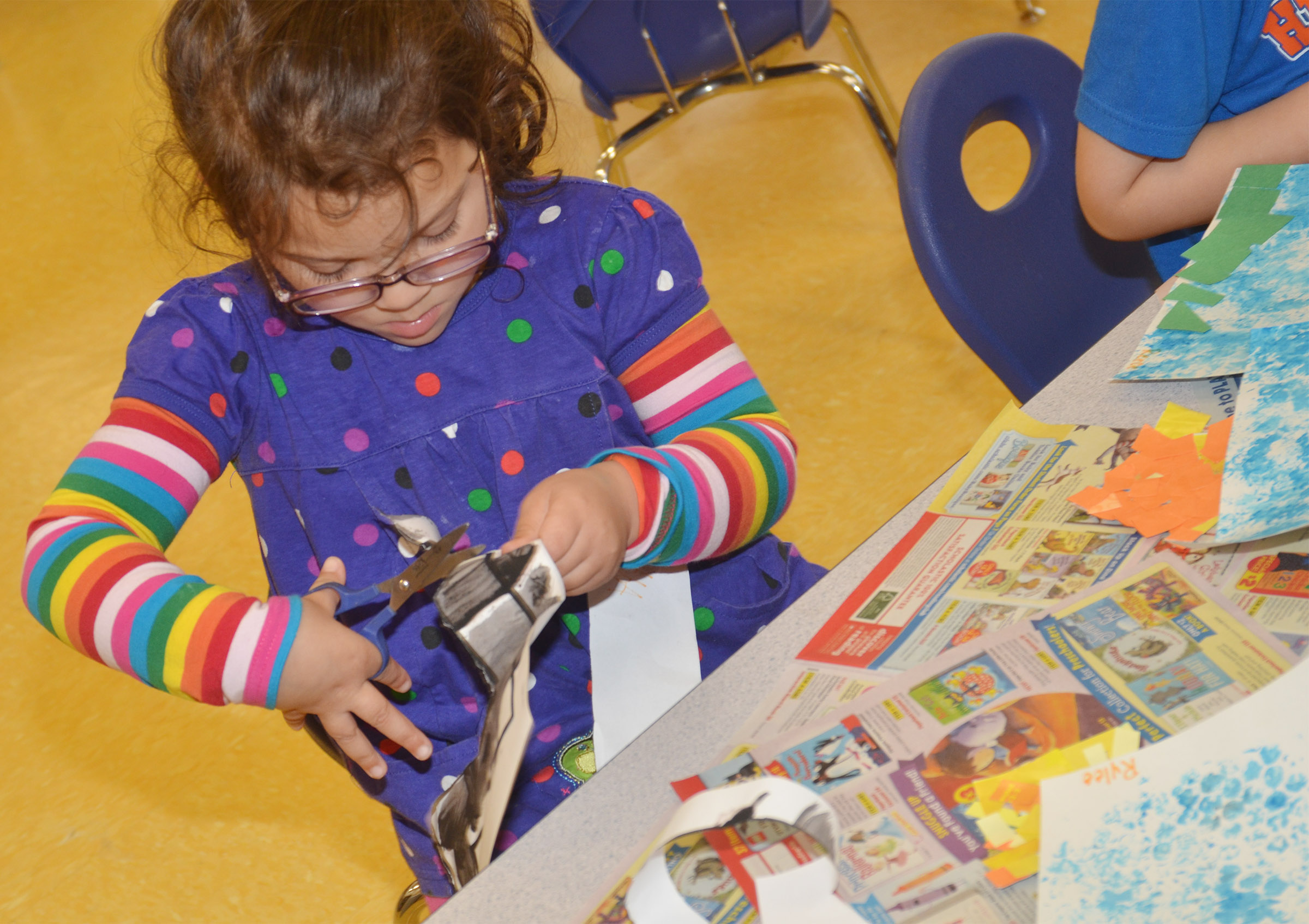 CES preschool student Addisyn Taylor cuts out her collage for the sun in her zebra craft.