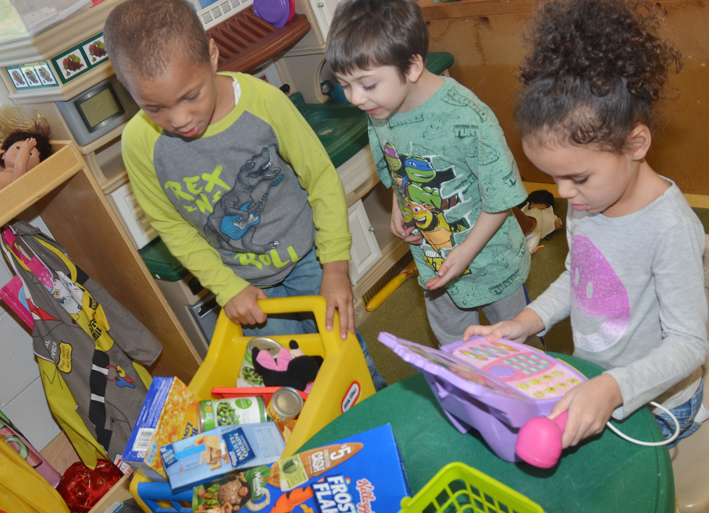 "CES preschool students Jamerius Miller, at left, and Josiah Dean shop while Adelyn Litsey waits to take their ""money."""