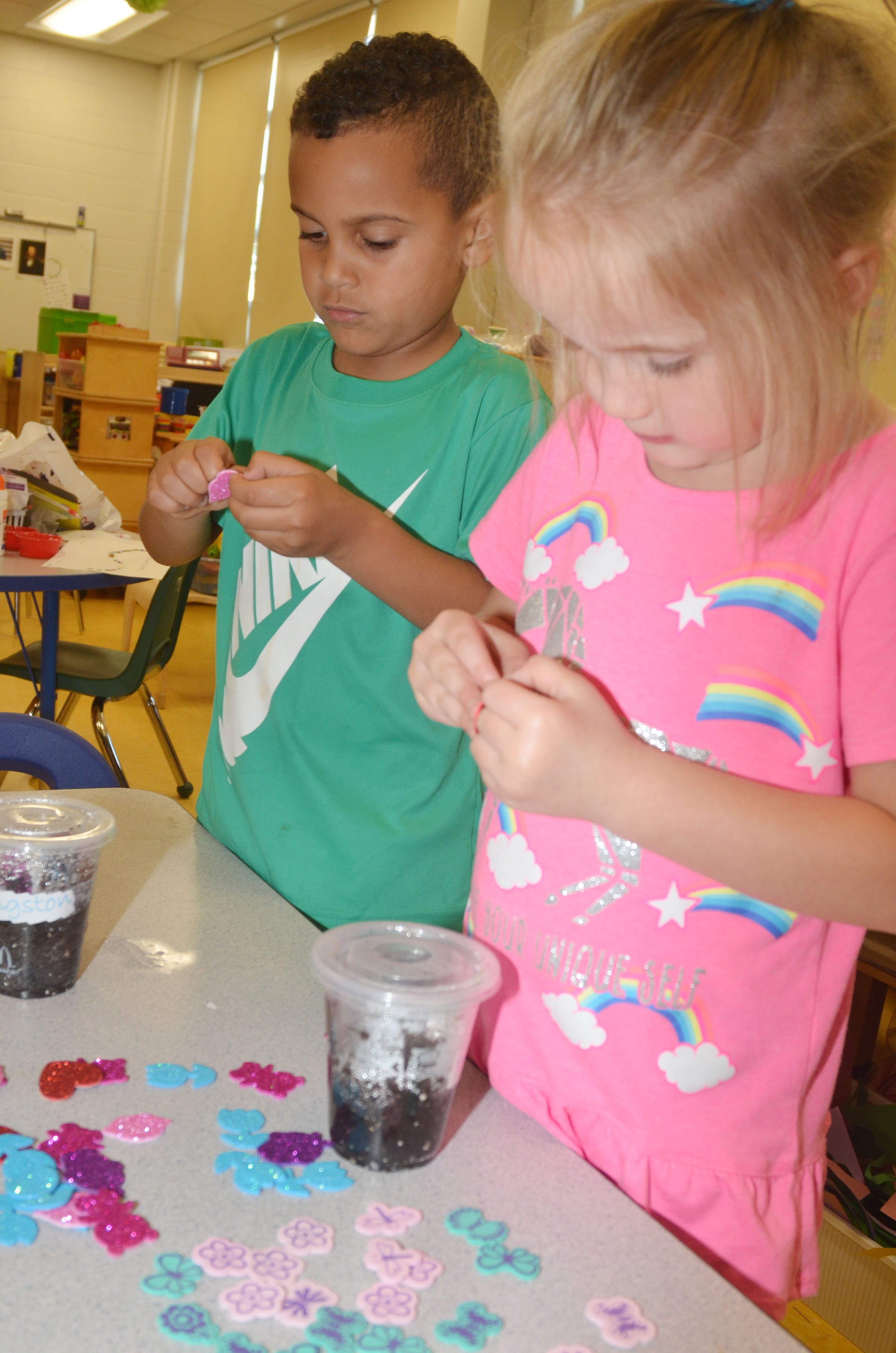 CES preschool students Kingston Cowherd, at left, and Trinity Dye decorate the cups in which they grew flowers for their mothers.