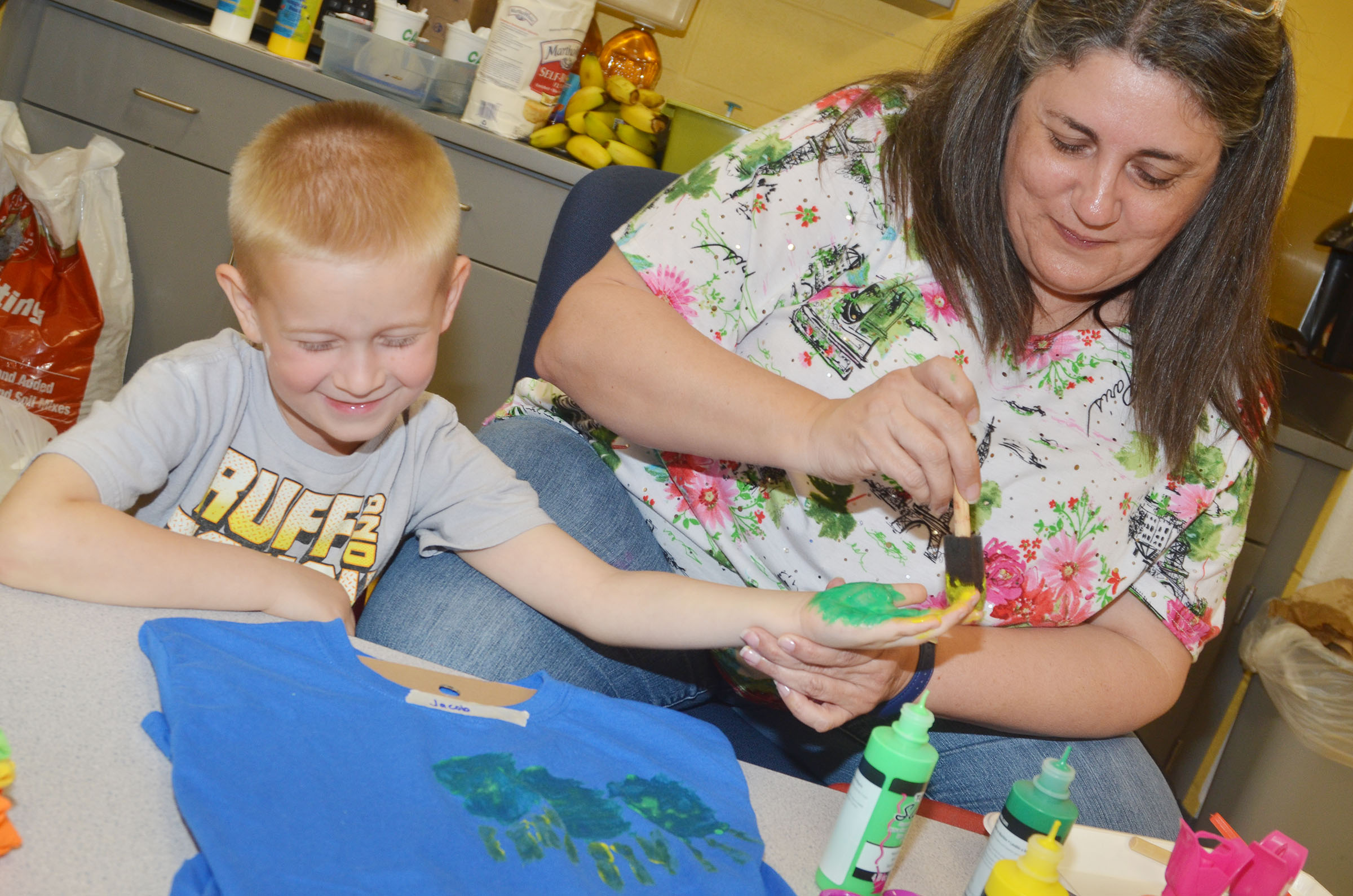 CES preschool teacher Sherry Cowherd helps Jacob Parrish make the t-shirt he will wear at the end of the year musical performance on Thursday, May 4.