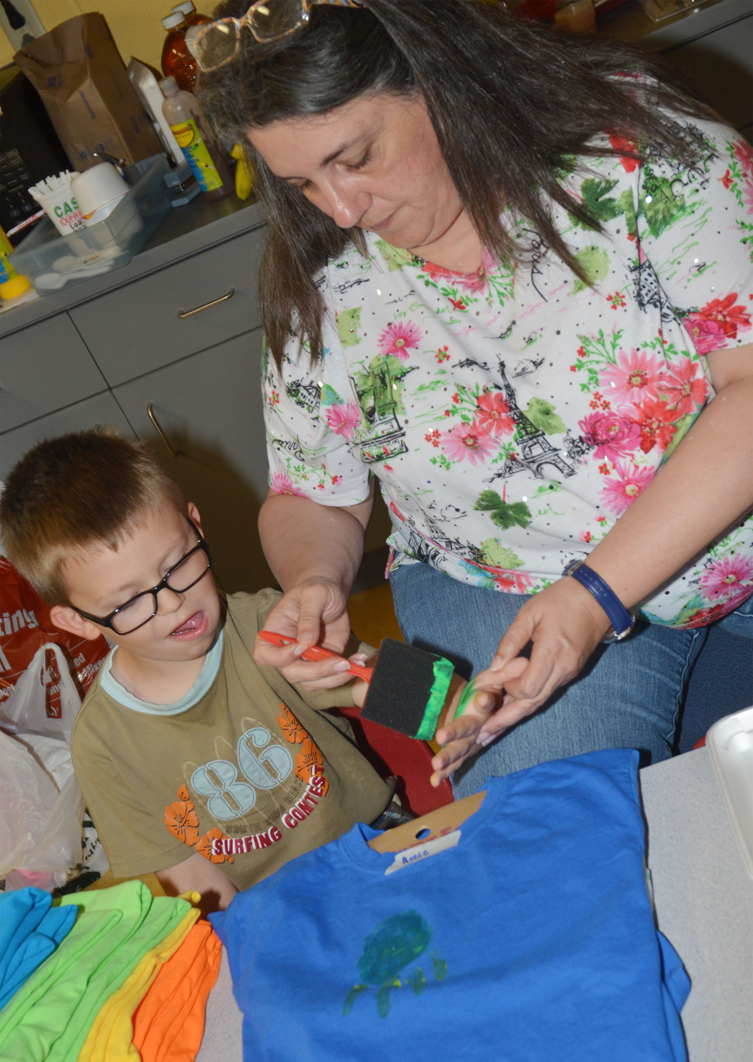 CES preschool teacher Sherry Cowherd helps Reece Williams make the t-shirt he will wear at the end of the year musical performance on Thursday, May 4.