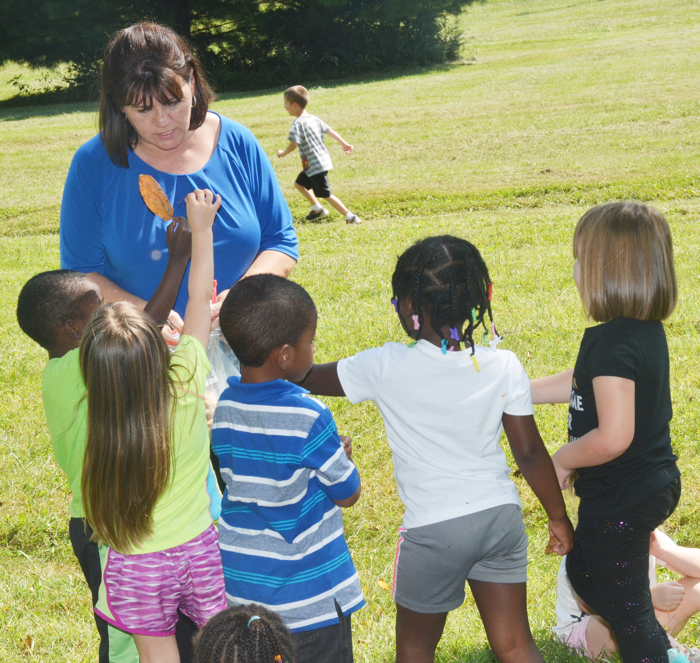 CES preschool teacher Denise Spencer collects leaves from her students during their nature walk.