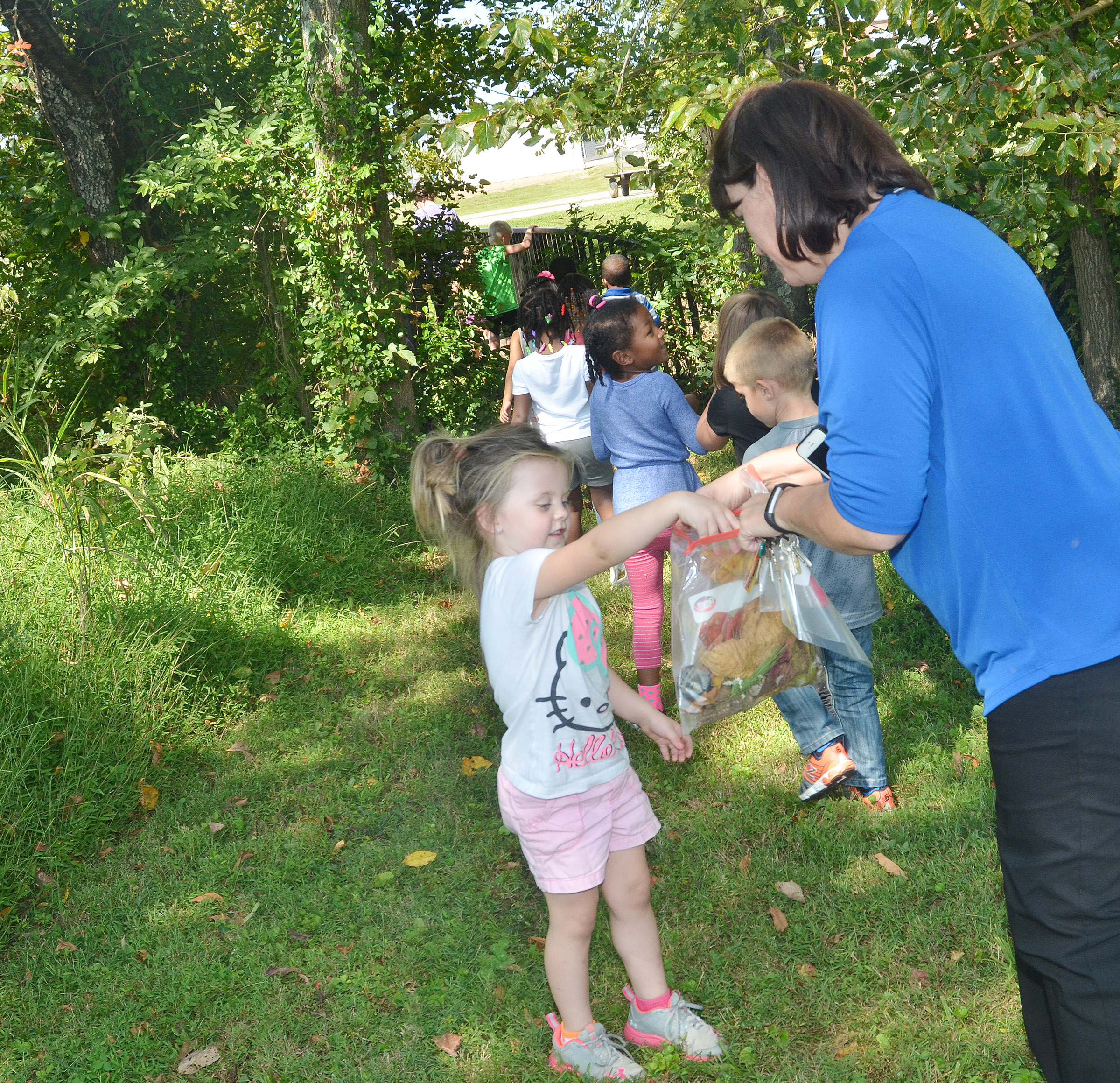 CES preschool teacher Denise Spencer collects leaves from student Tori Clark during their nature walk.