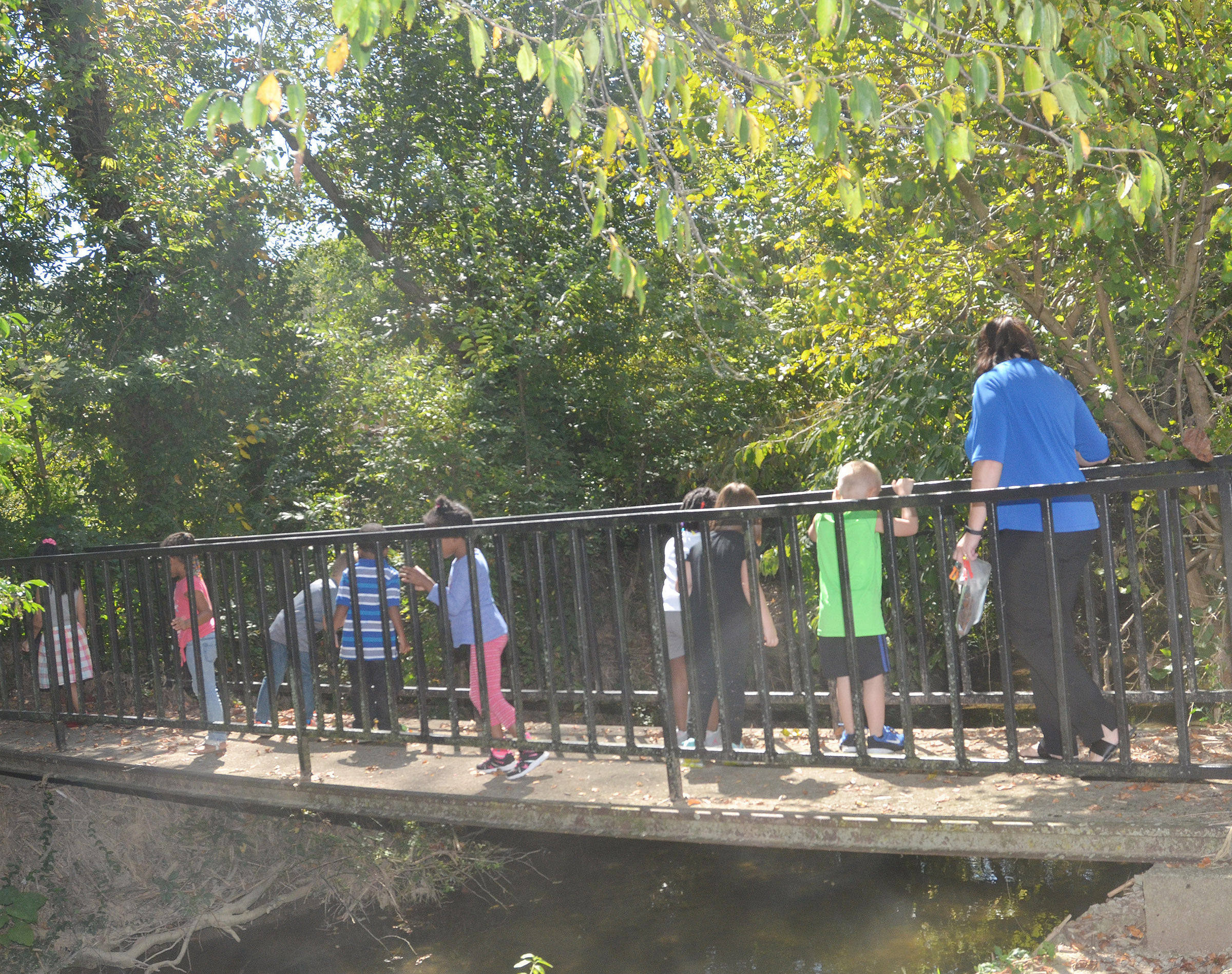 CES preschool teacher Denise Spencer walks with her students across a bridge during a nature walk.