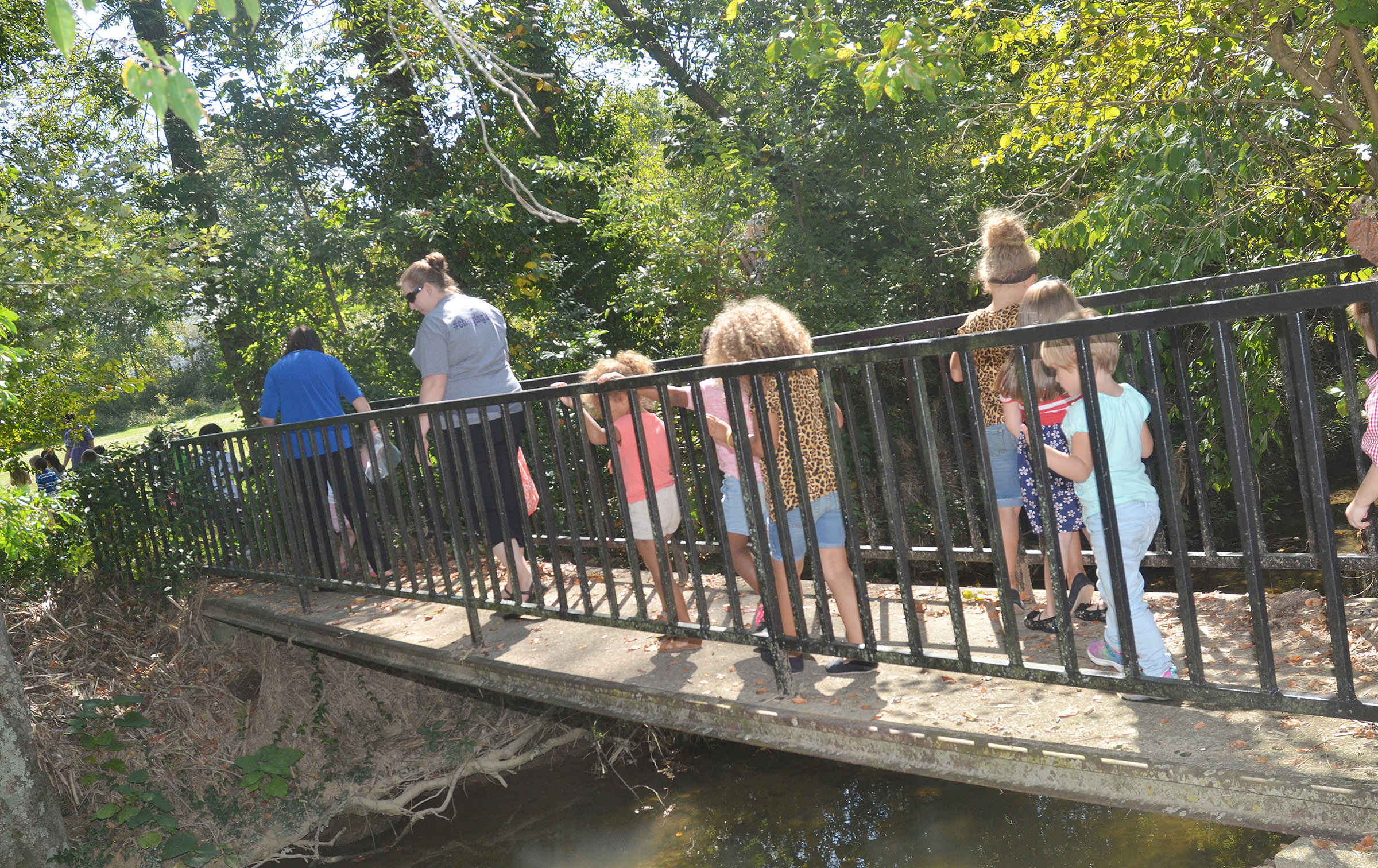 CES preschool teachers Denise Spencer, at left, and Julie Shelton walk with their students across a bridge during their nature walk.