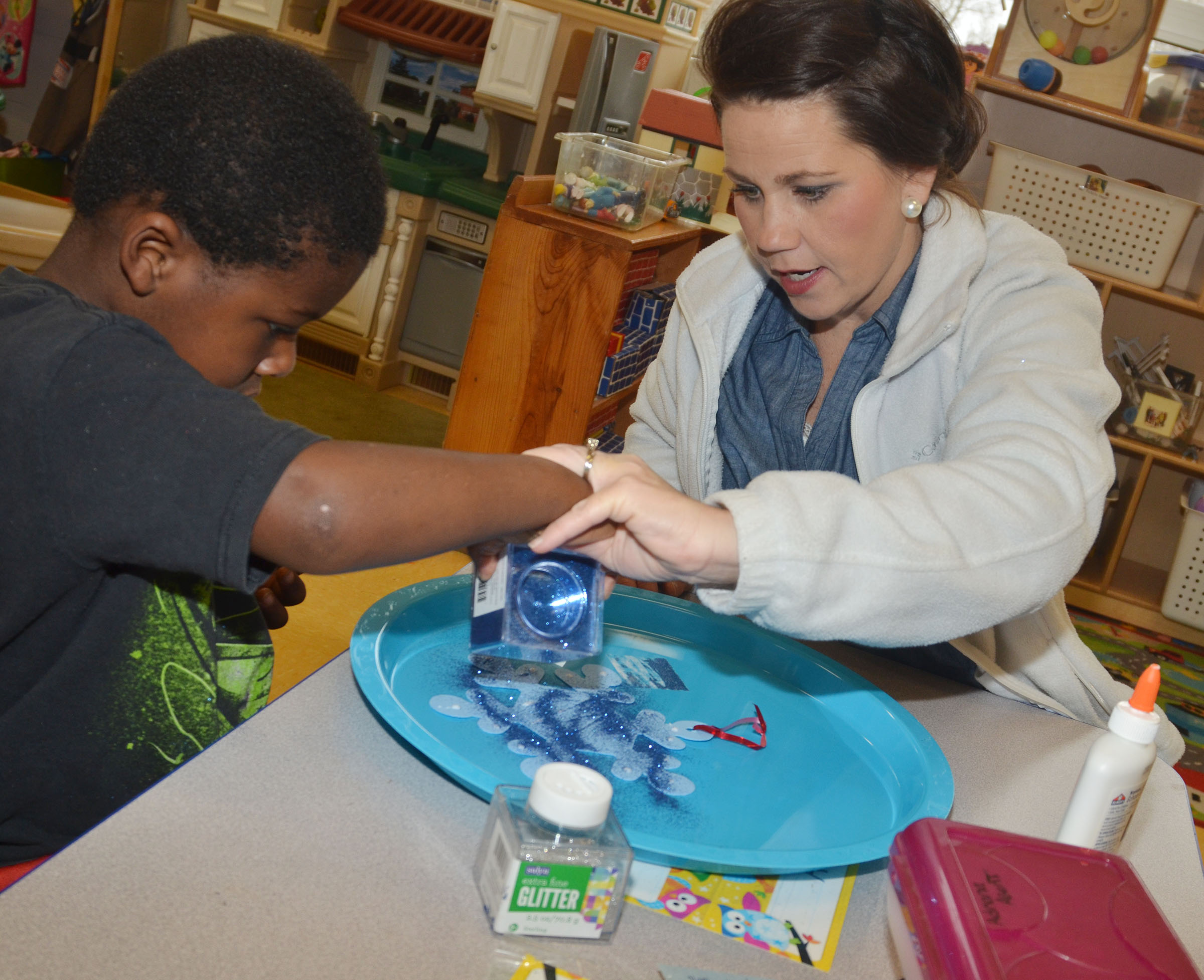 CES preschool assistant Beth Sandidge helps LaTayvion Brown make a snowflake ornament.