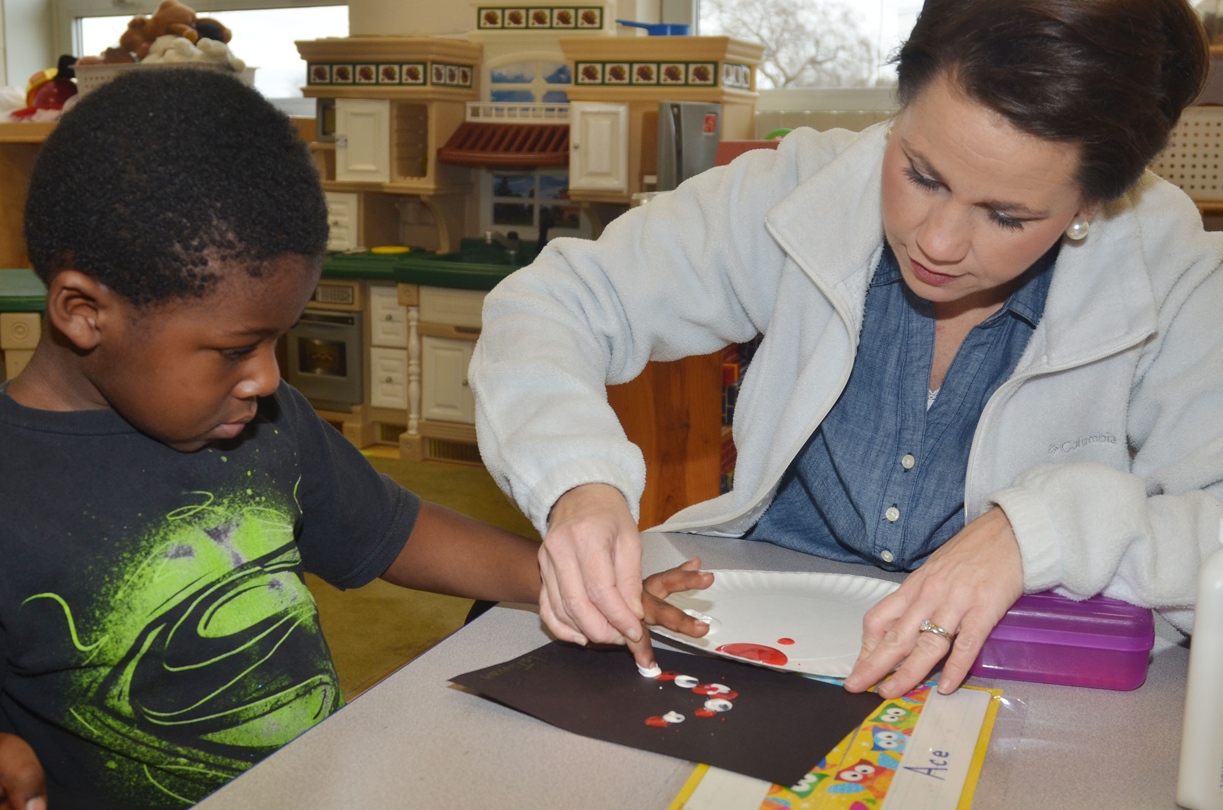 CES preschool assistant Beth Sandidge helps LaTayvion Brown make a Santa Claus with red and white paint.