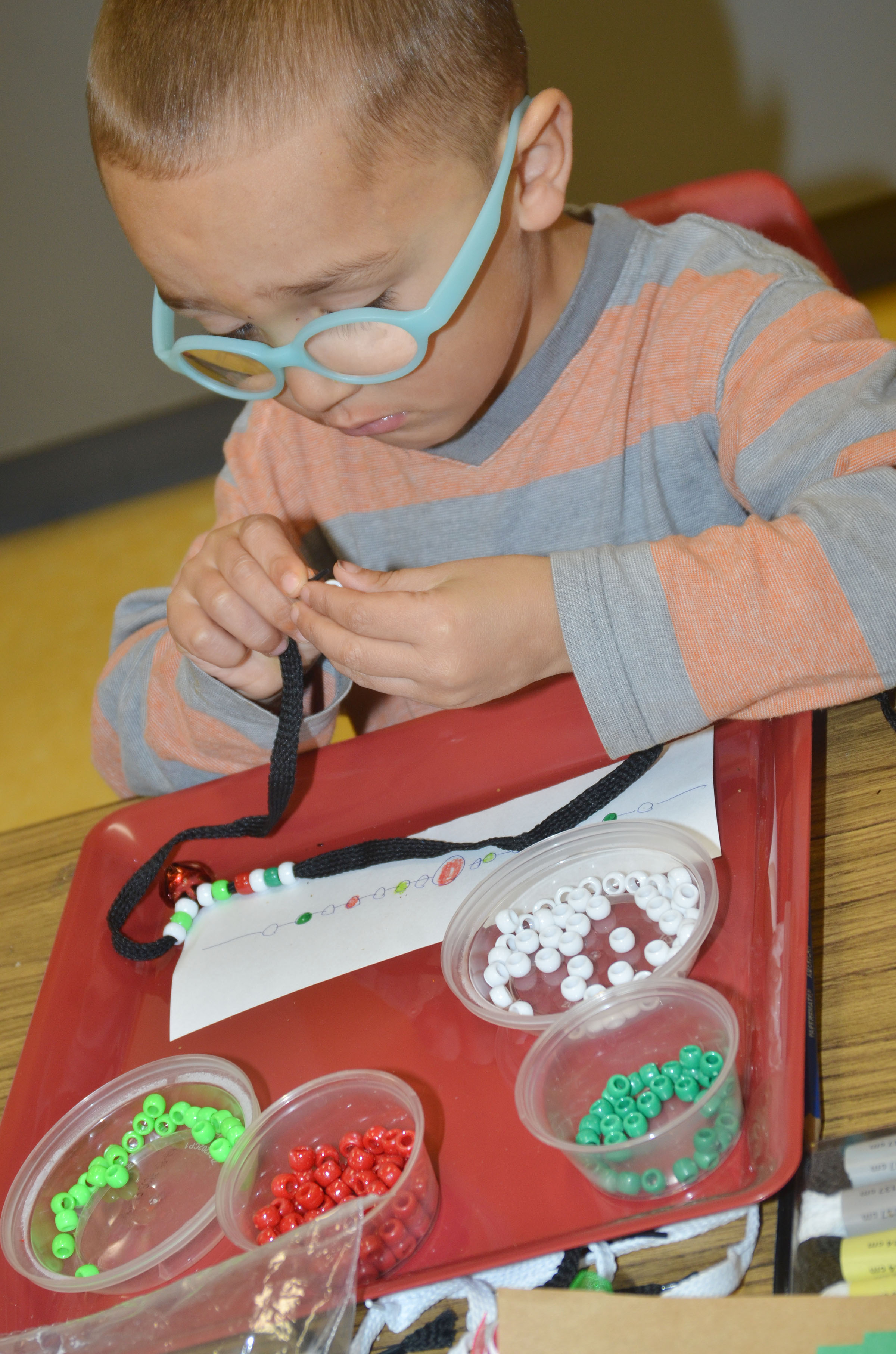 CES preschool student Chanler Mann makes a jingle bell necklace.