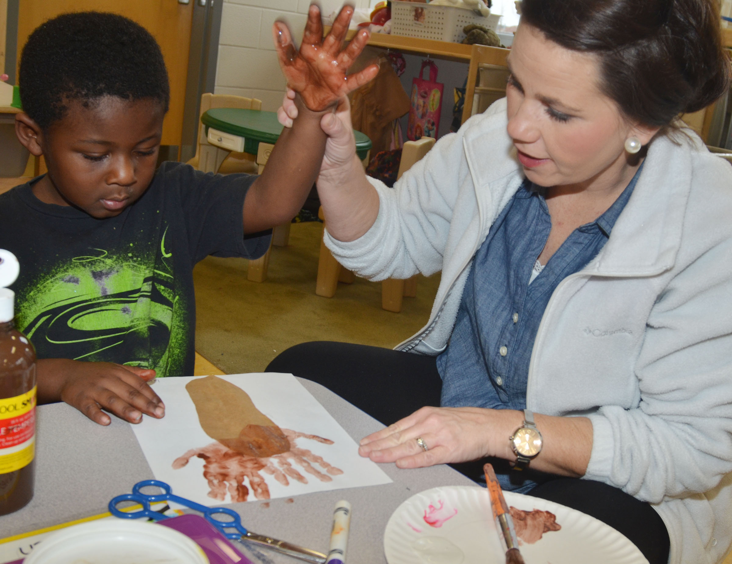 CES preschool assistant Beth Sandidge helps LaTayvion Brown make a reindeer.
