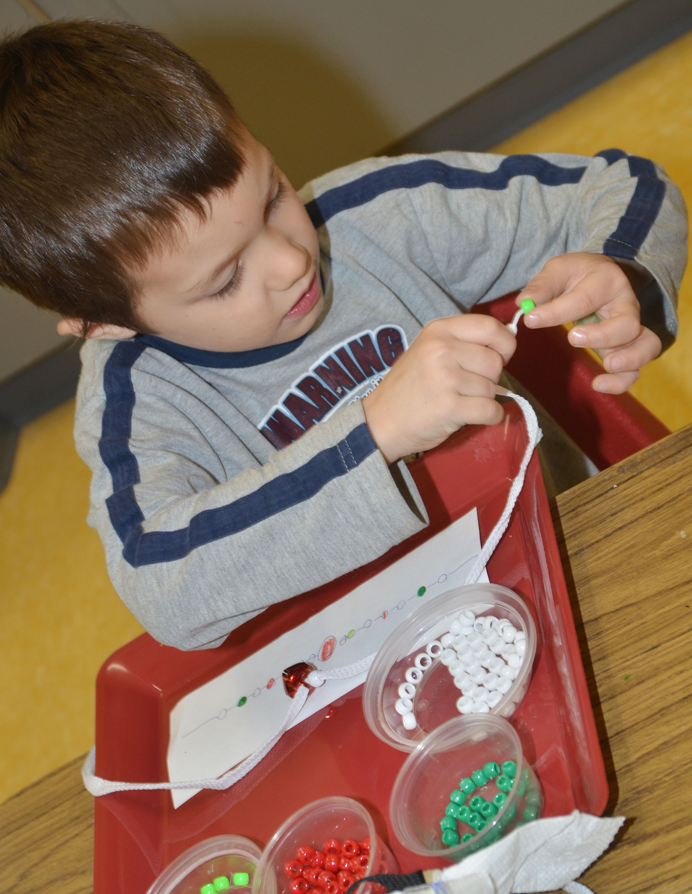 CES preschool student Levi Ritchie makes a jingle bell necklace.