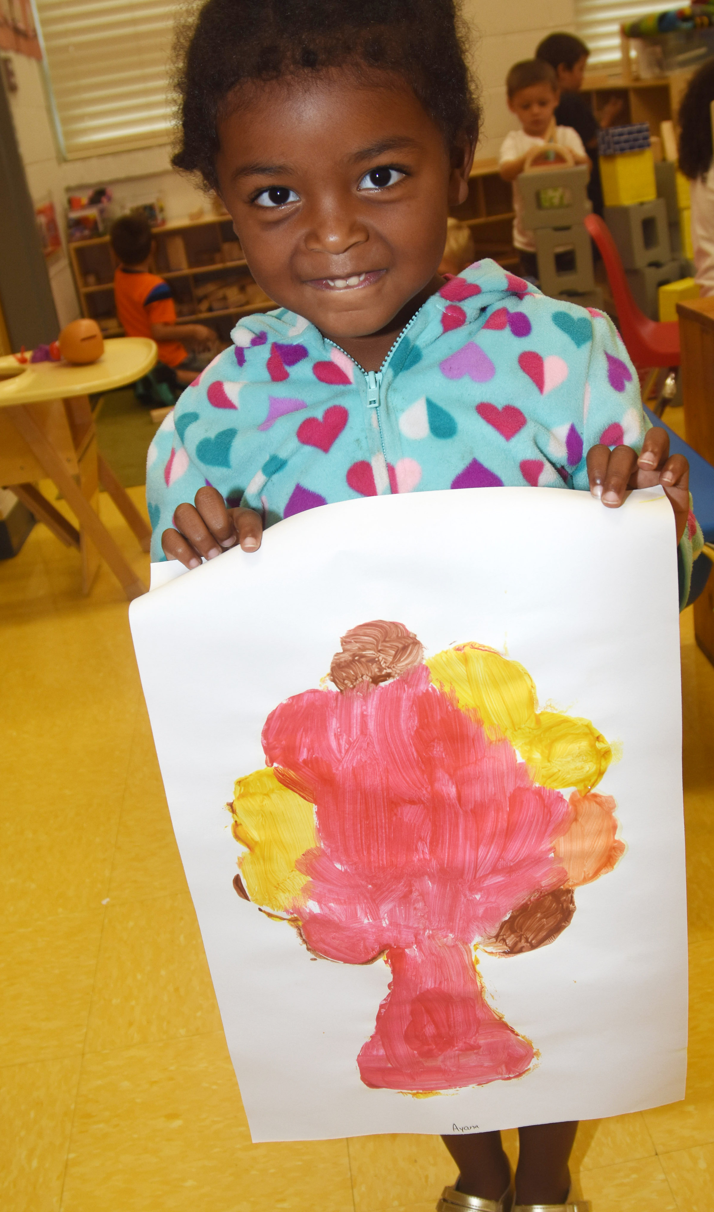 CES preschool student Ayana Flores holds her fall tree.
