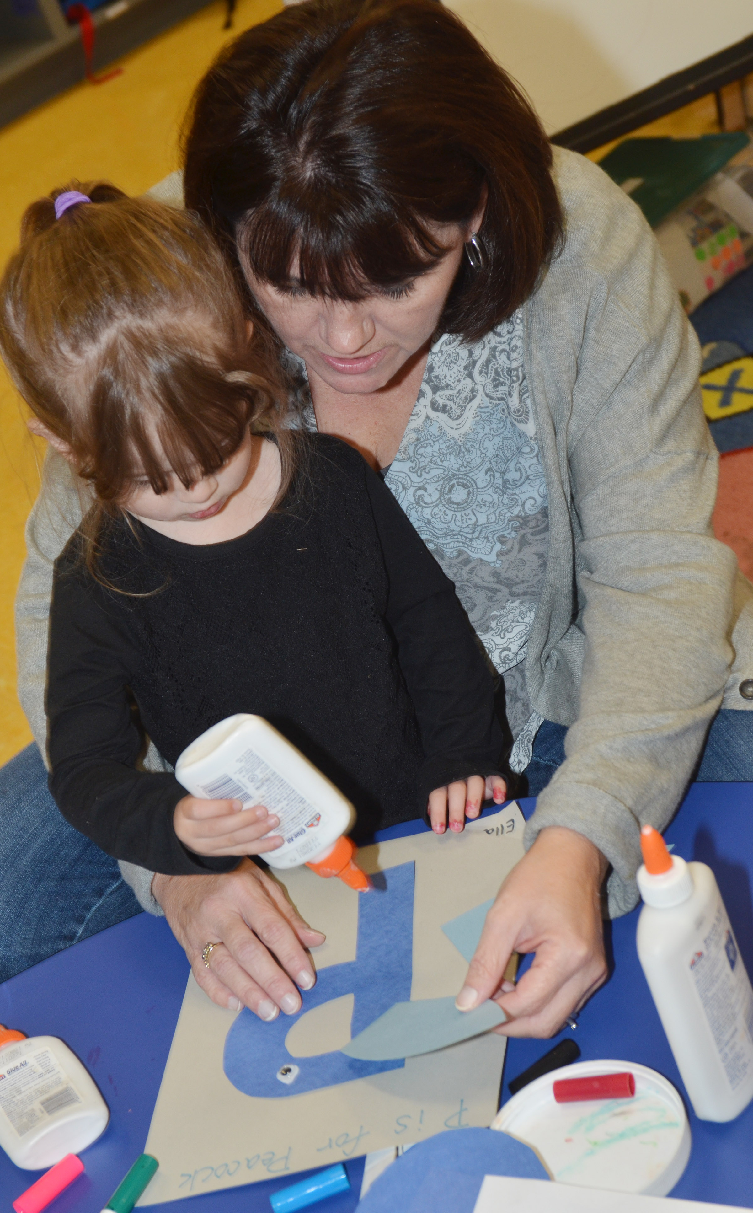 CES preschool teacher Denise Spencer helps student Ella Woodbury glue her peacock together.