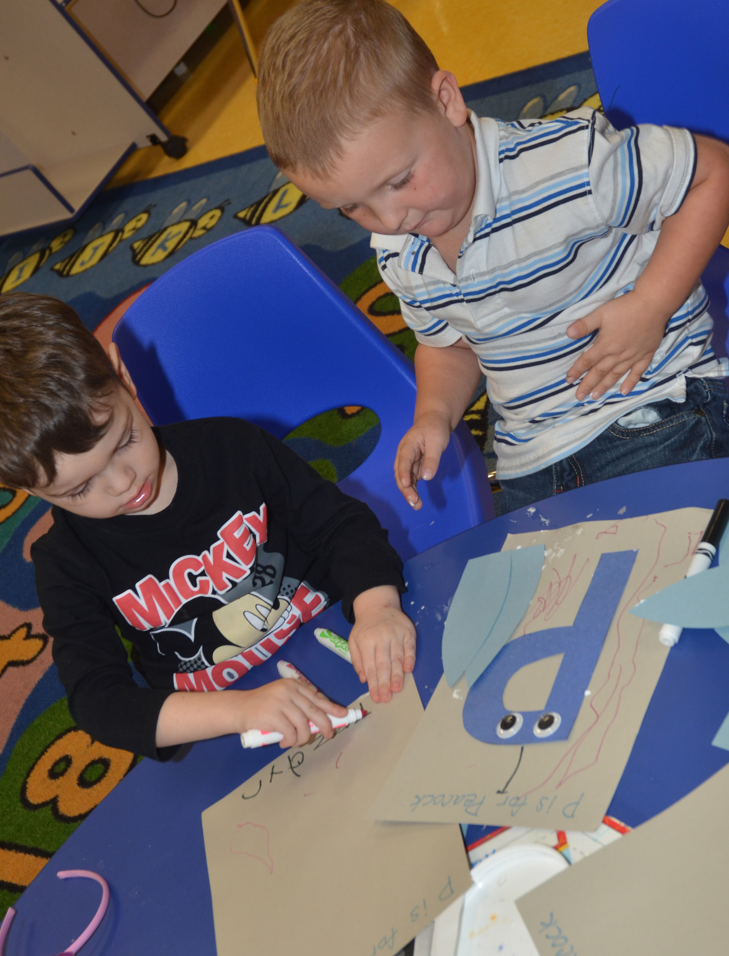 CES preschool students Elijah Puyear, at left, and Gannon Scott work on their peacocks.