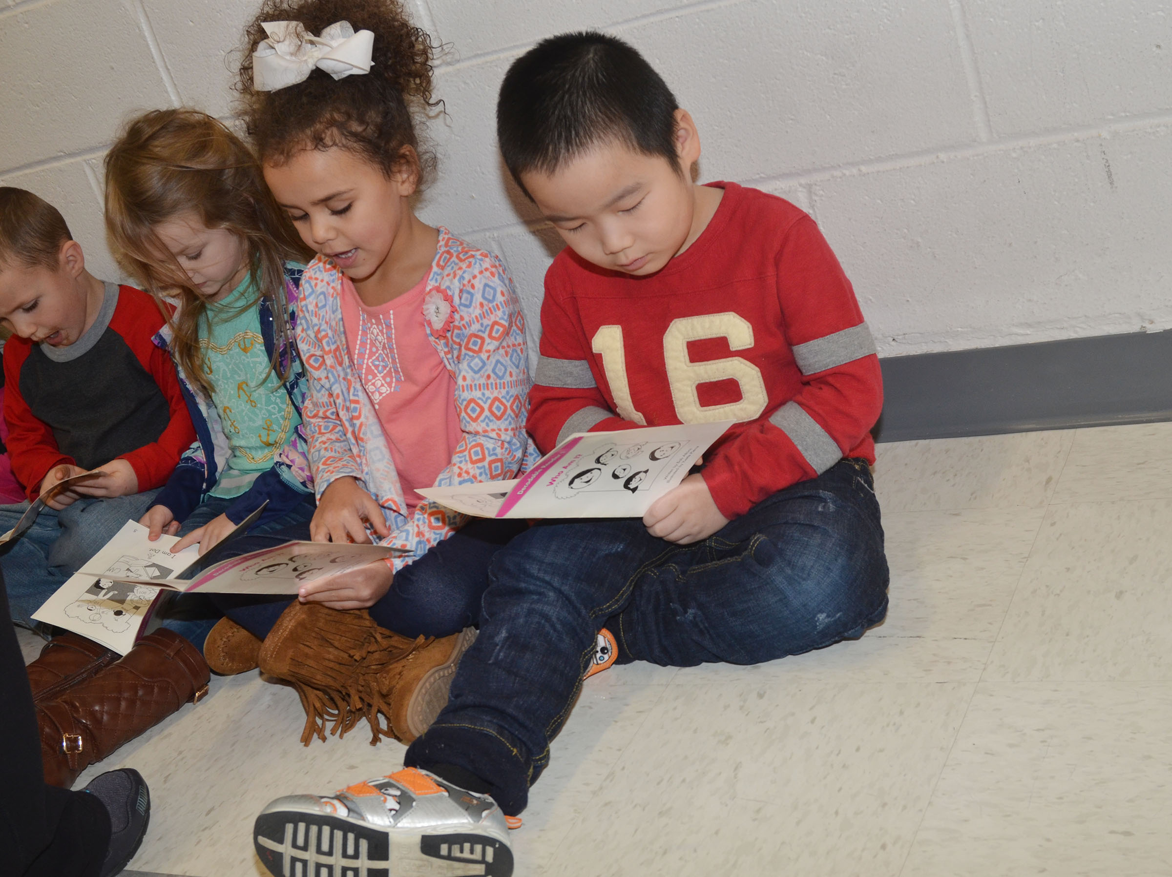 CES preschool student Calvin Yang and his classmates read together.