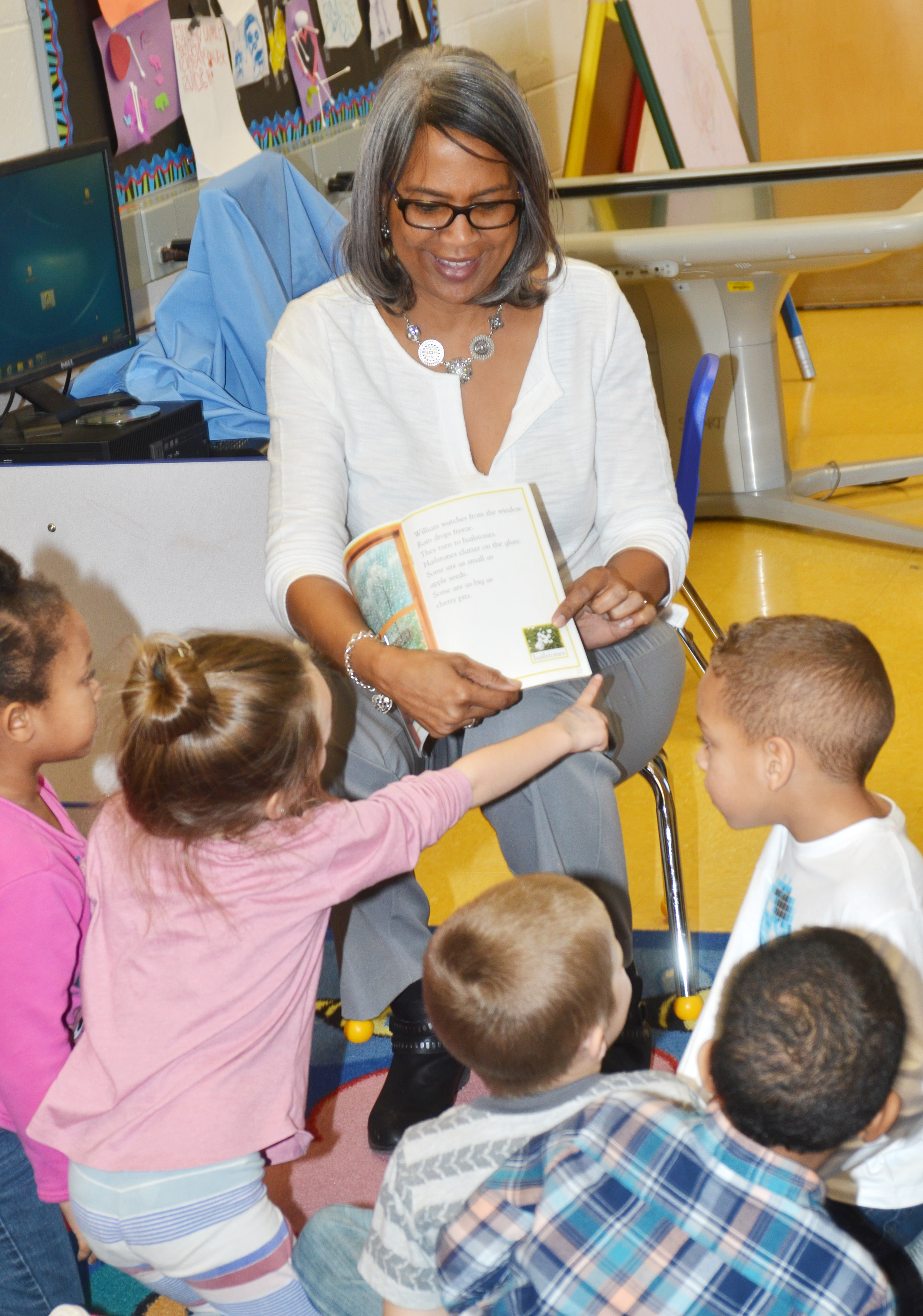 Doretha Sanders, who previously taught third-grade students at CES but is now an assistant principal, reads a book about weather to CES preschool students.