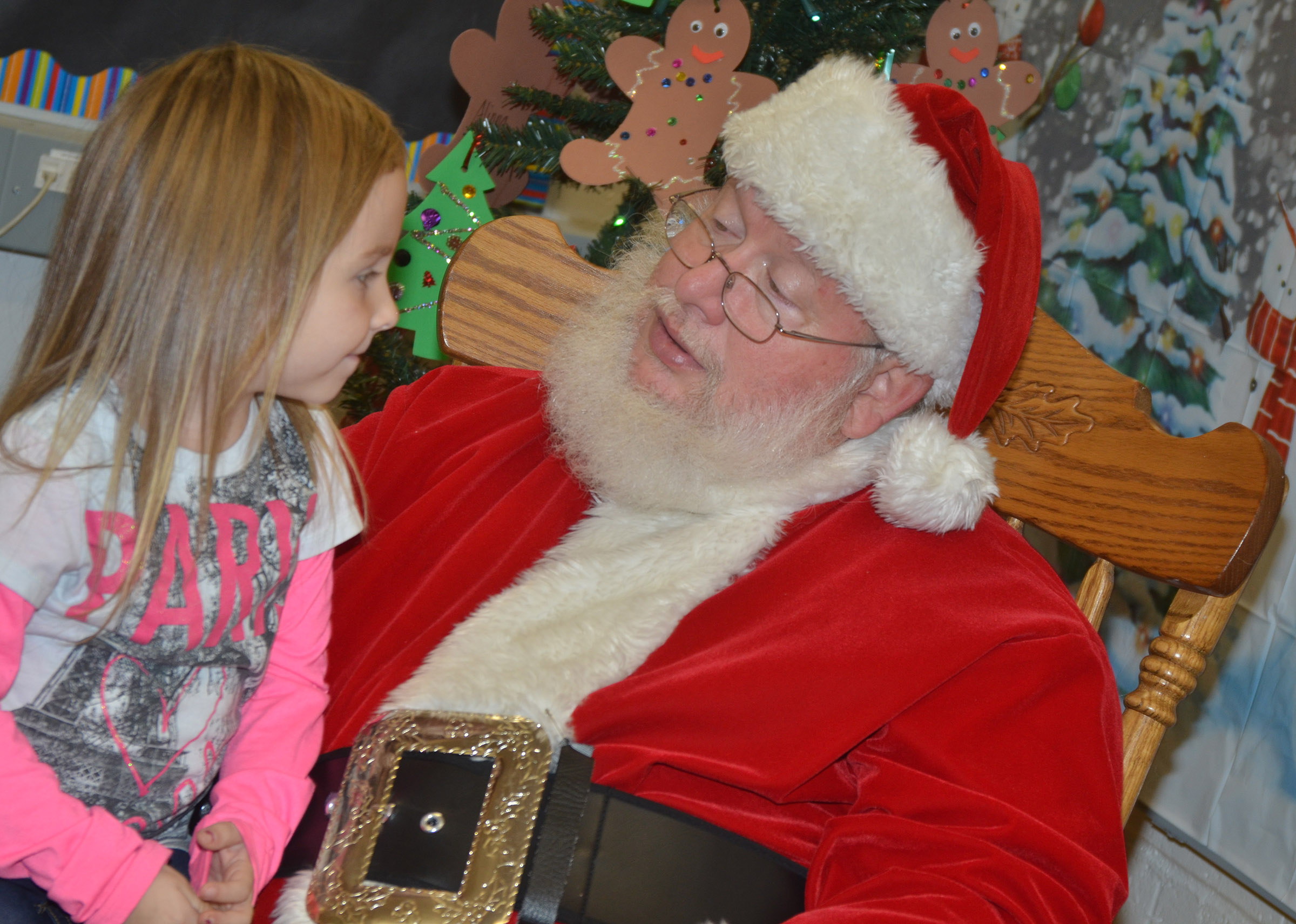 CES preschool student Tabitha Leggett tells Santa she has been good.