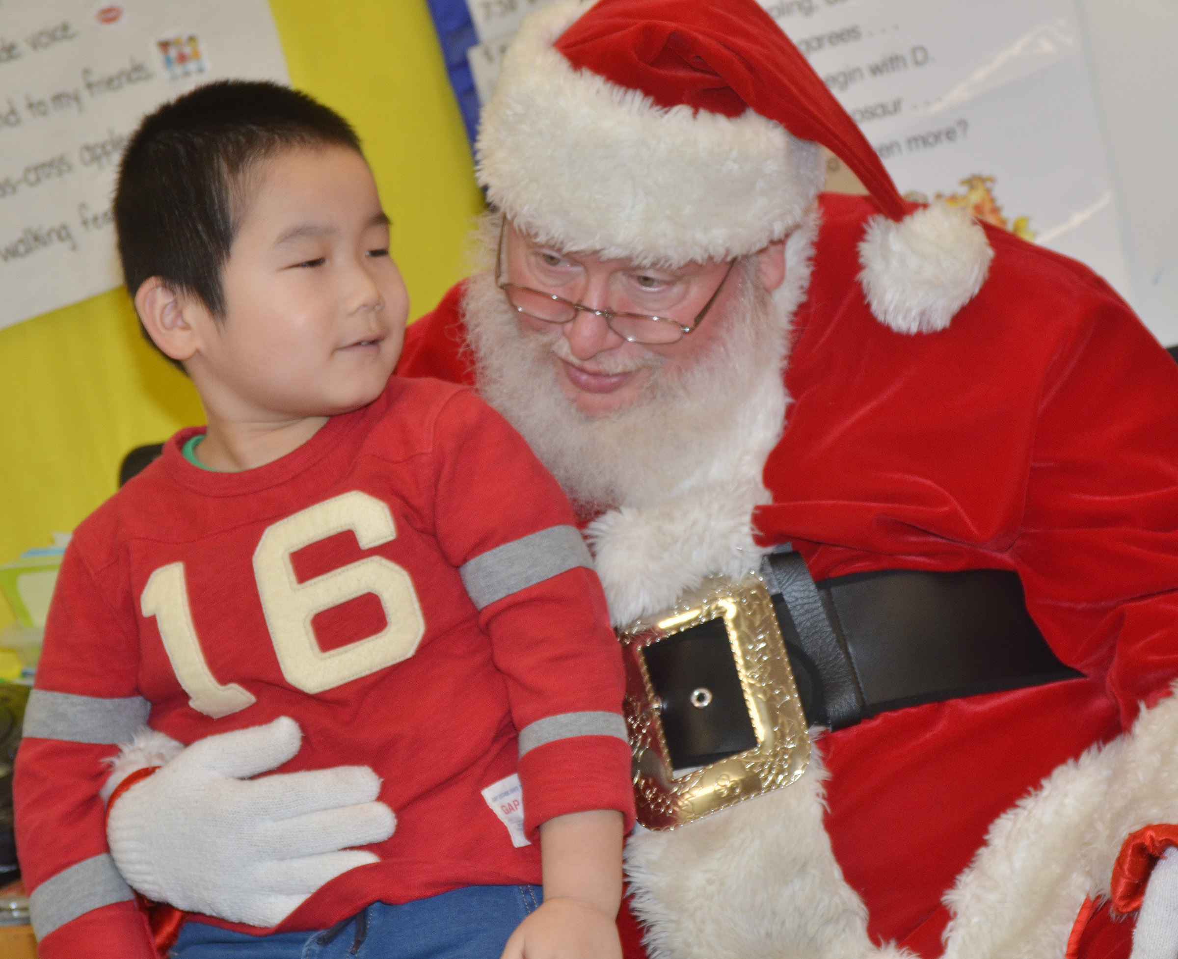 Santa leans in as CES preschool student Calvin Yang talks to him.
