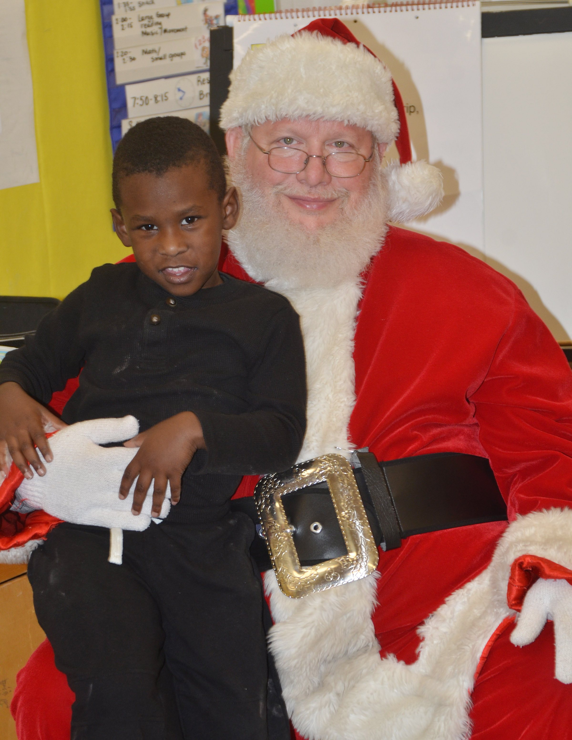 CES preschool student Trezdyn Tonge smiles for a photo with Santa.