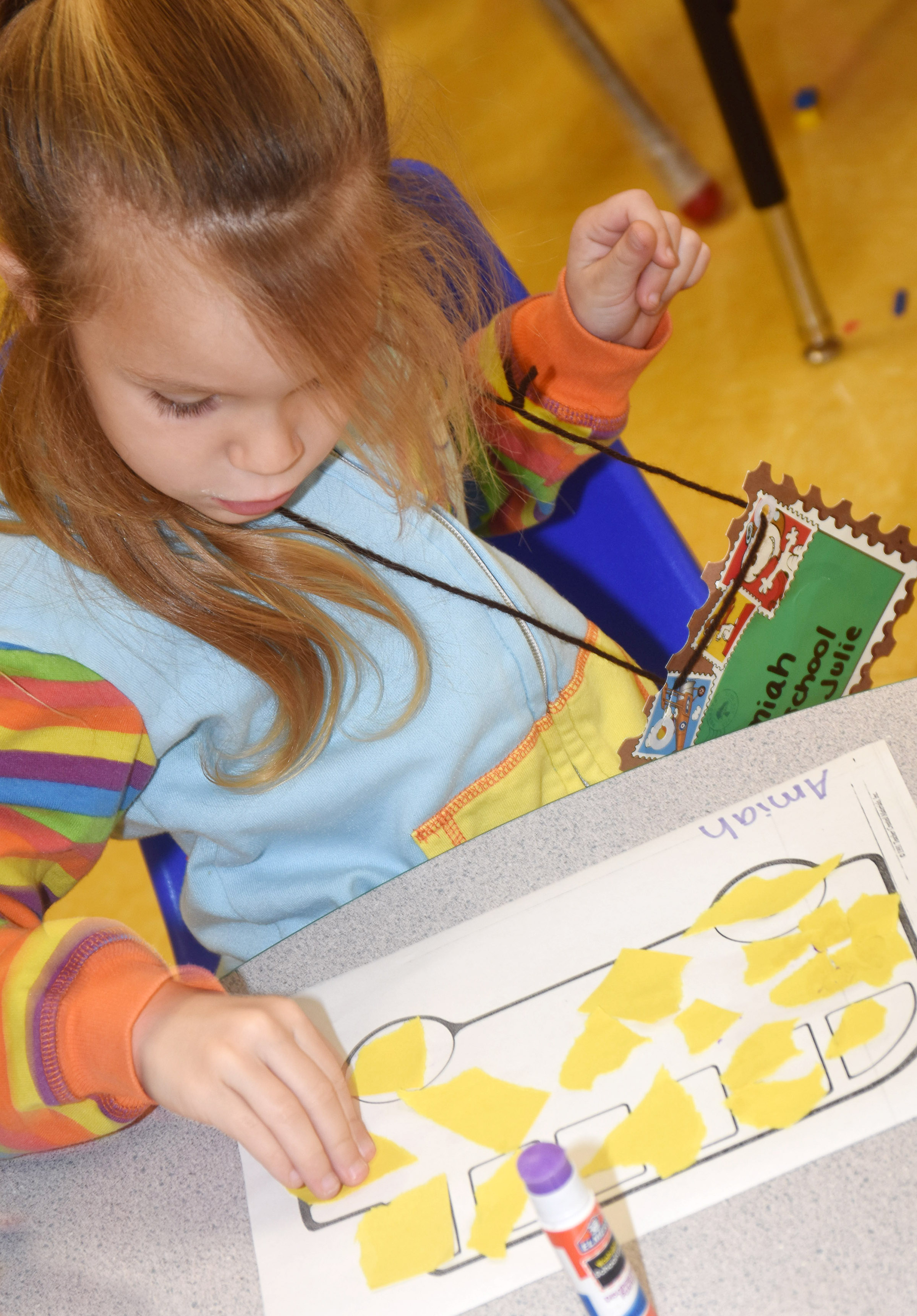 CES preschool student Amiah Carmicle glues windows on her school bus.