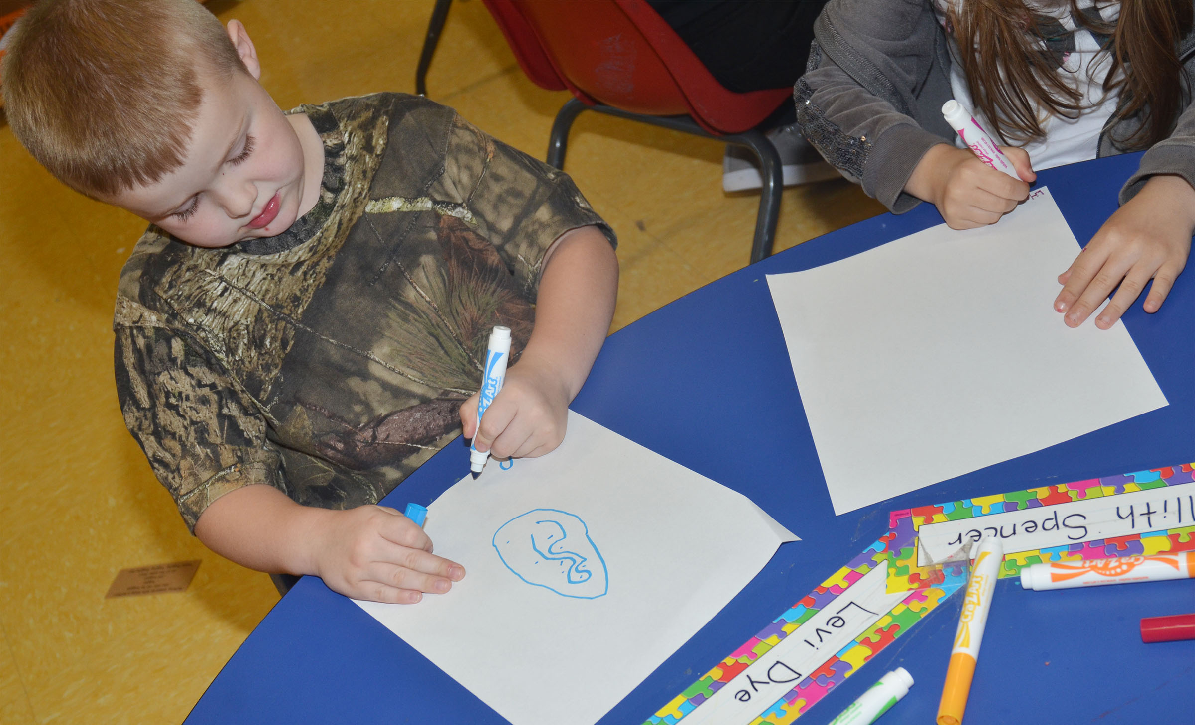CES preschool student Levi Dye draws a picture of his favorite part of school.