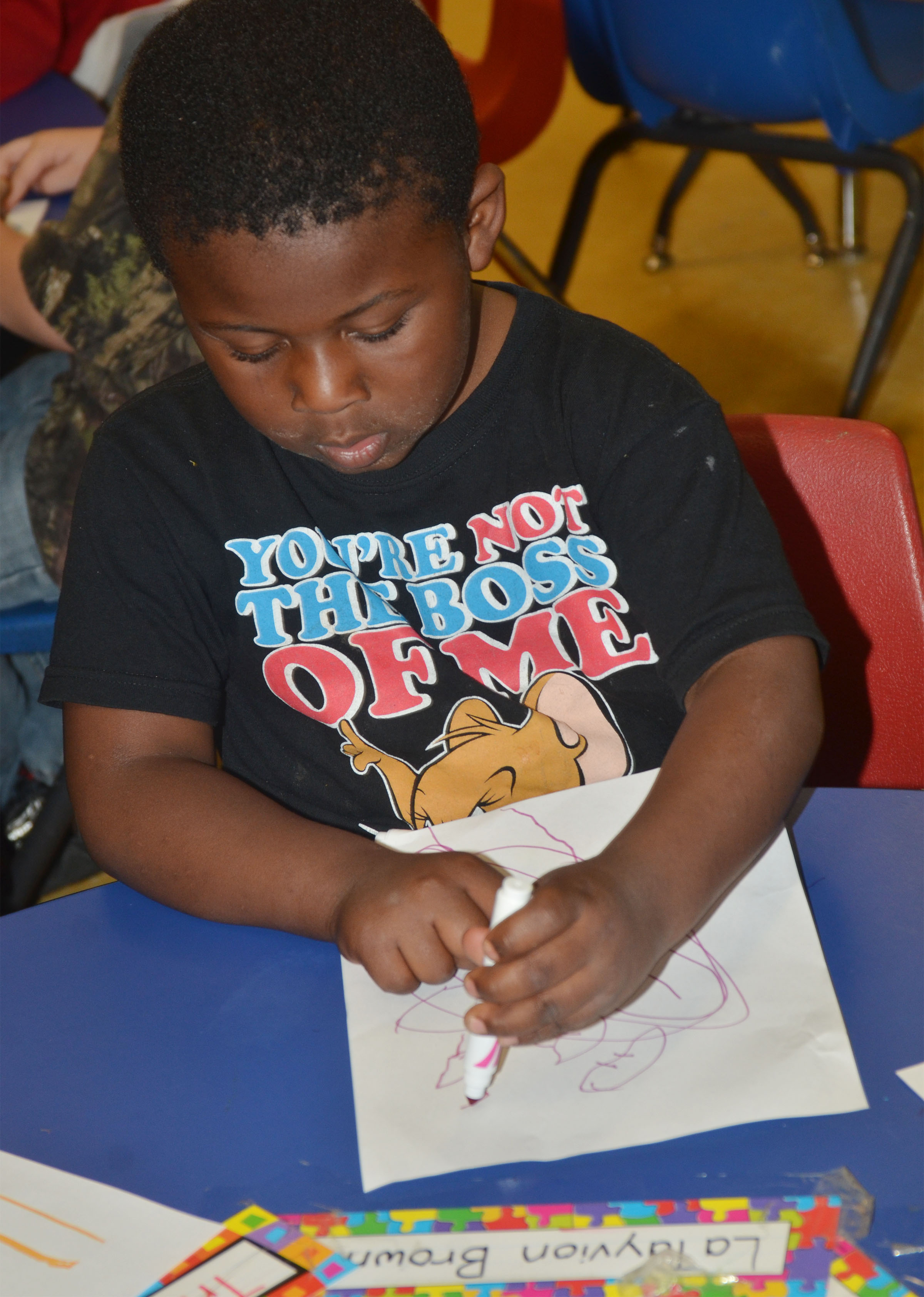 CES preschool student LaTayvion Brown draws a picture of his favorite part of school.