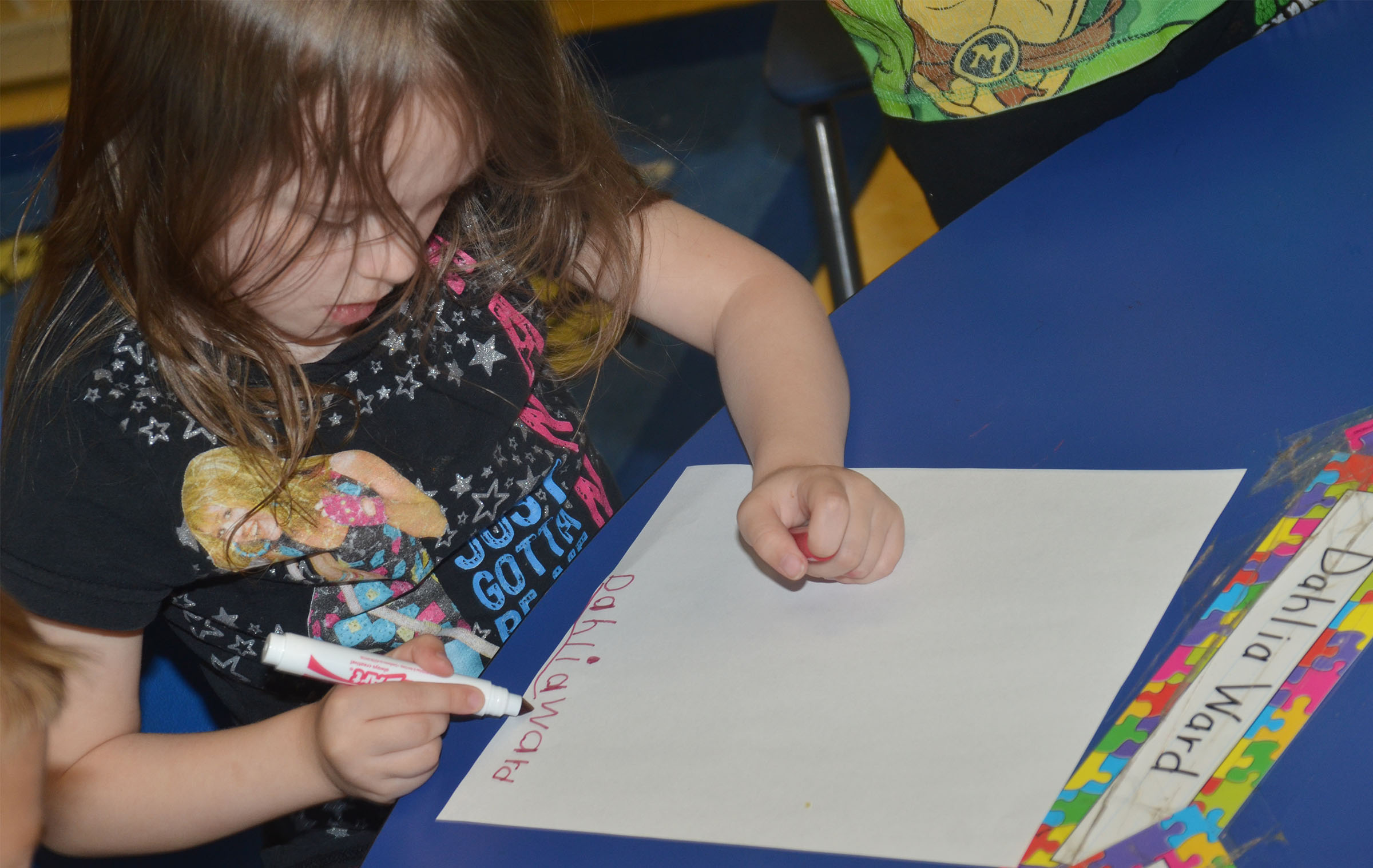 CES preschool student Dahlia Ward writers her name.