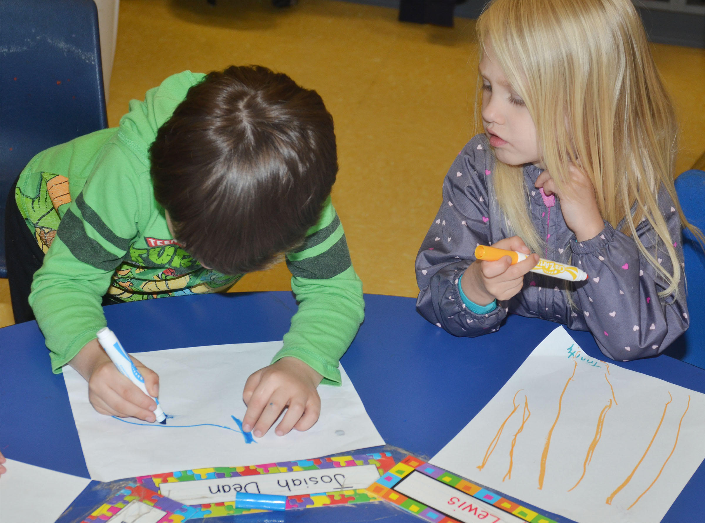 CES preschool student Josiah Dean, at left, and Trinity Lewis draw their favorite part of school.