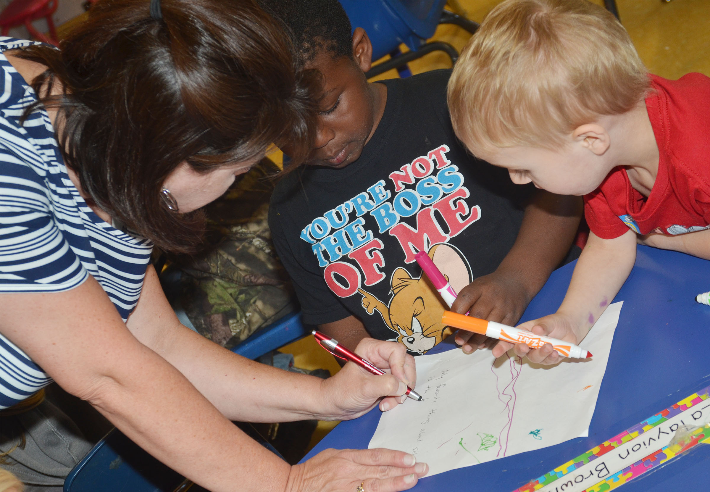 CES preschool teacher Denise Spencer helps LaTayvion Brown, center, and Chase Russell write about their favorite part of school.
