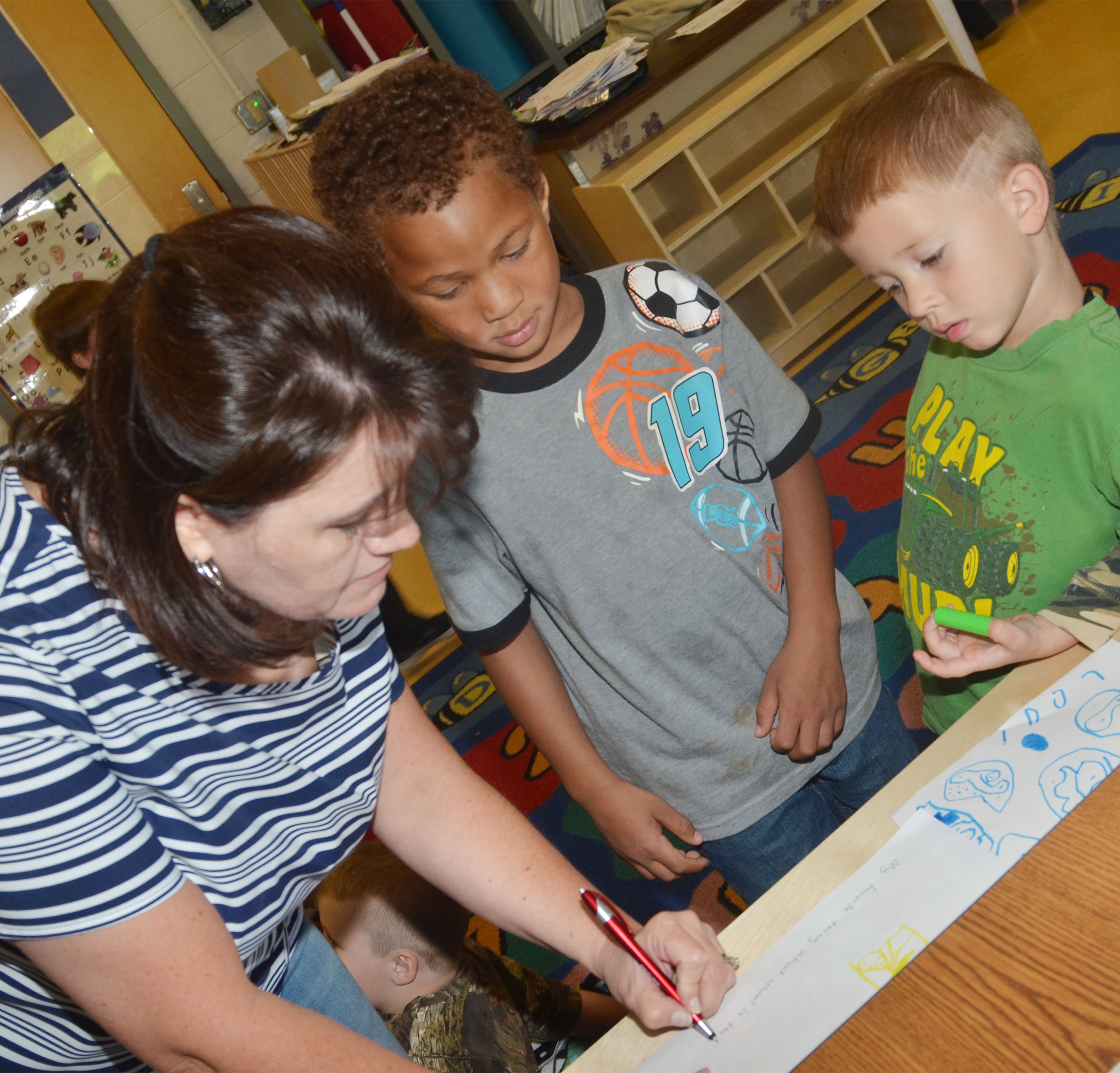 CES preschool teacher Denise Spencer helps students Jamerius Miller, center, and Andrew Stout write about their favorite part of school.