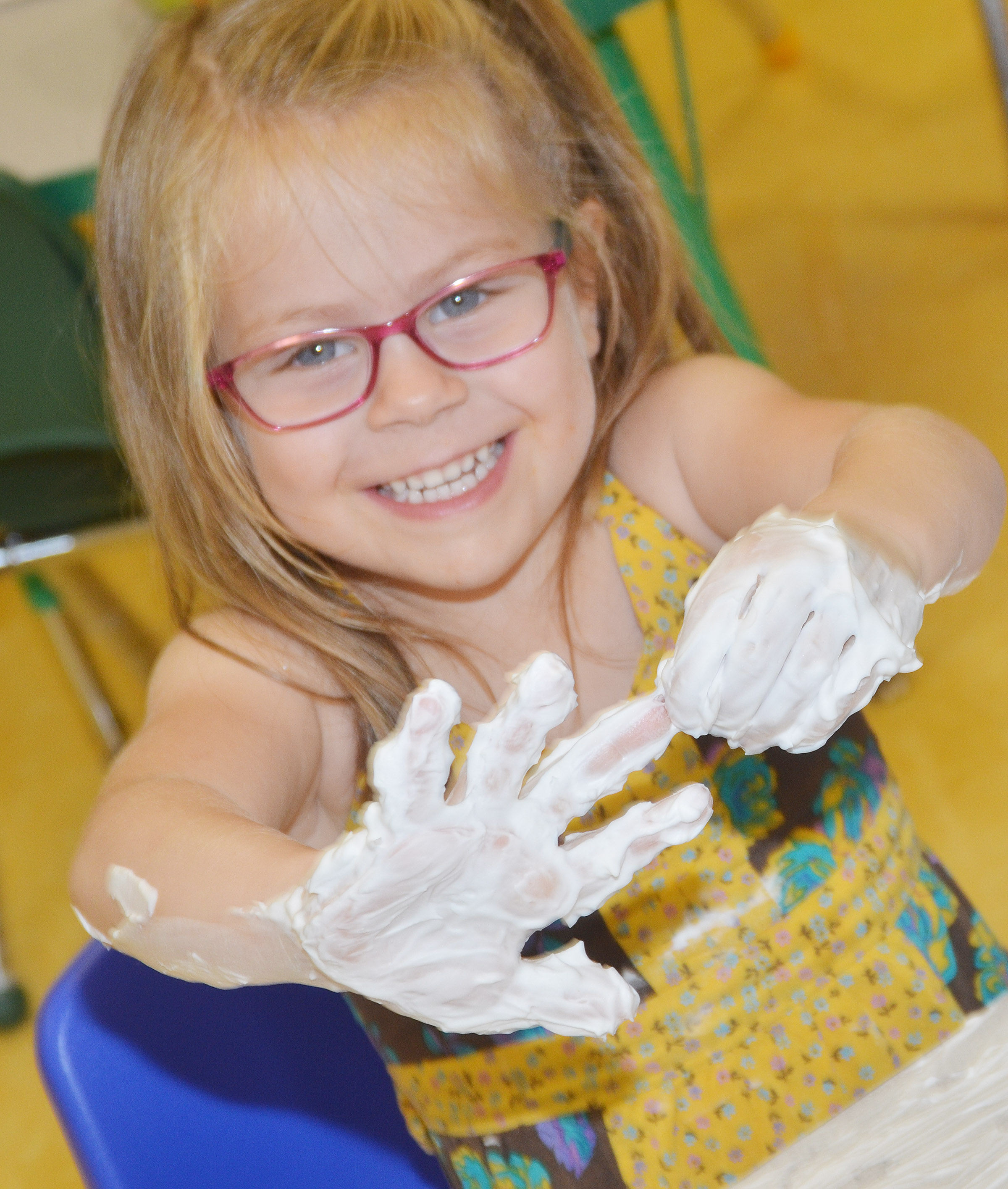CES preschool student Charlotte Coots smears shaving cream in her hands.