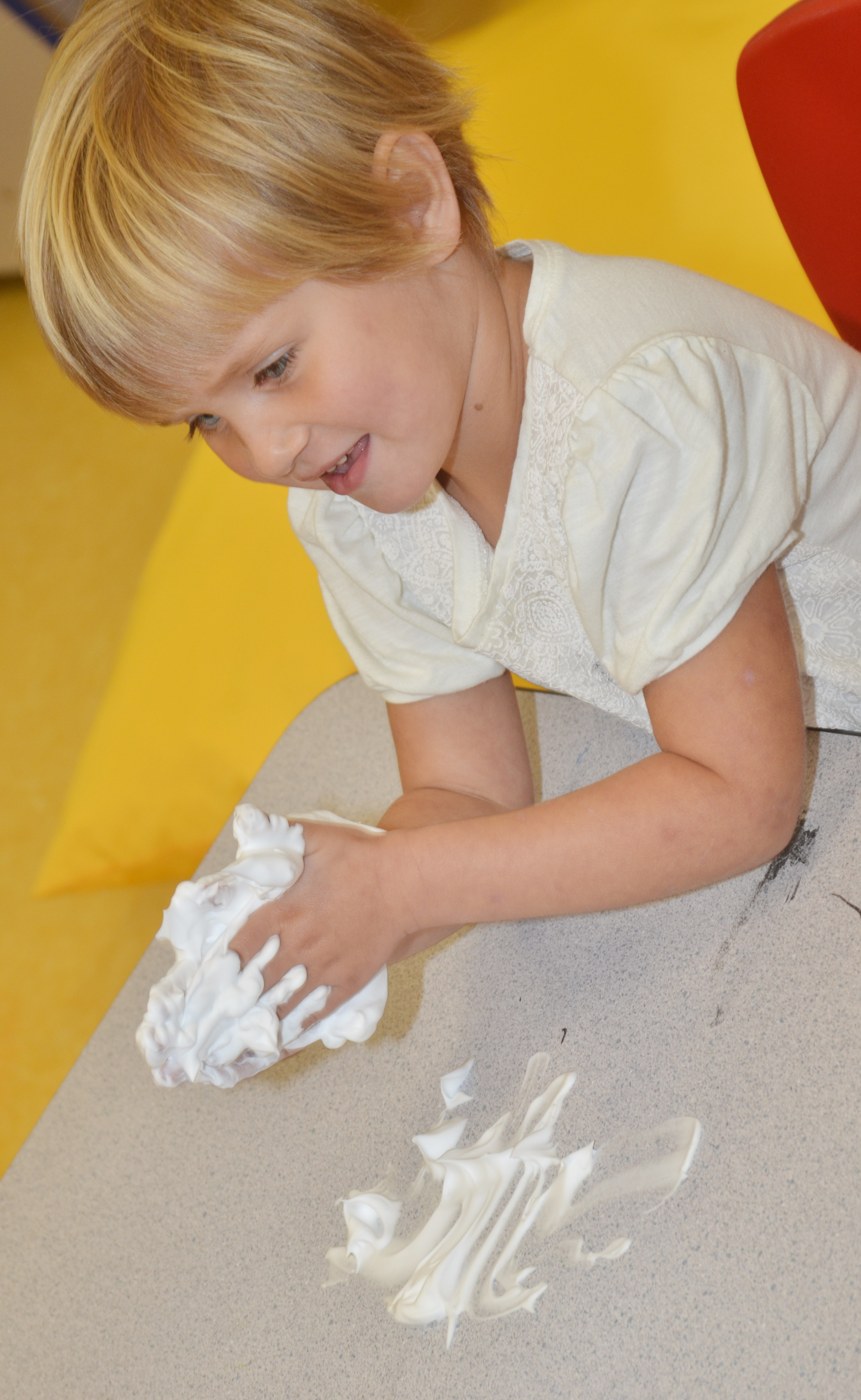 CES preschool student Elliana Morton feels shaving cream in her hands.