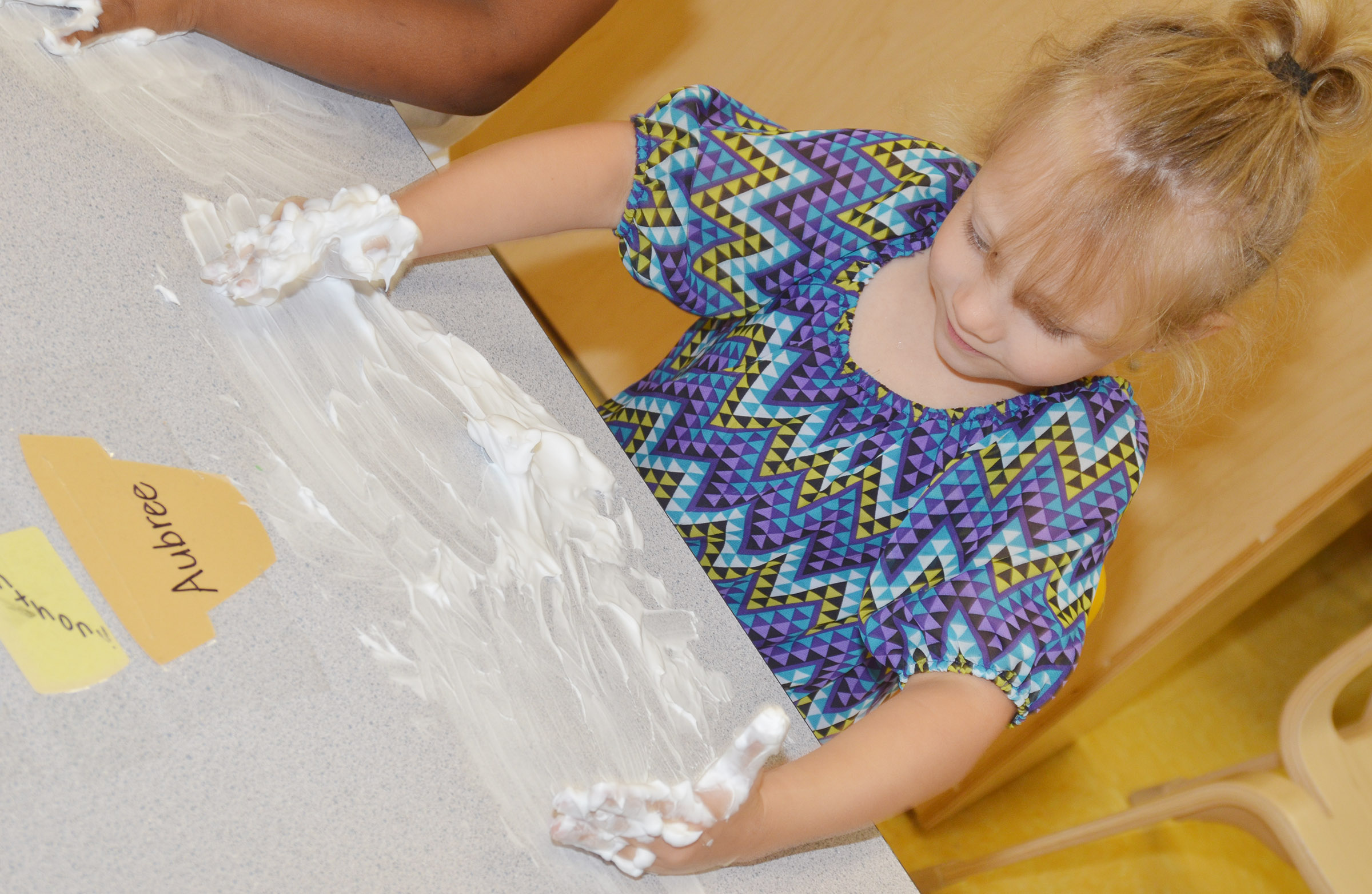 CES preschool student Aubree Hall rubs shaving cream on her desk.