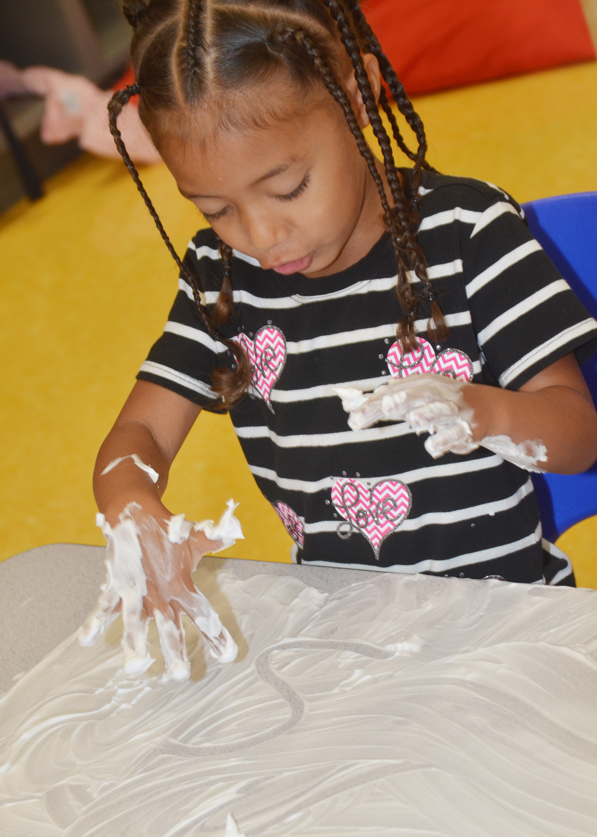 CES preschool student Onyx Hunter draws an S in her shaving cream.