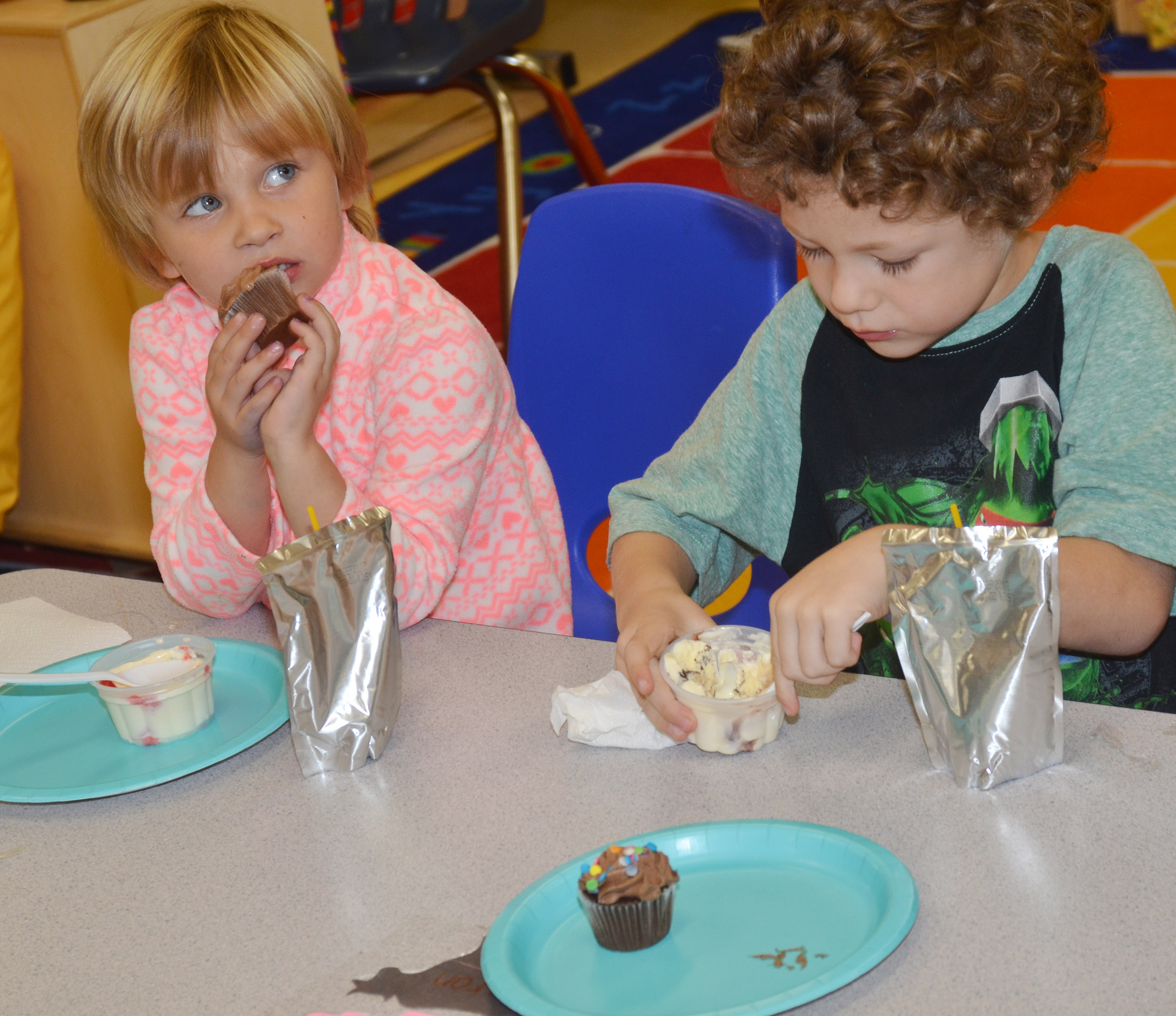 CES preschool students Elliana Morton, at left, and Zyron Young enjoy their ice cream and cupcakes.