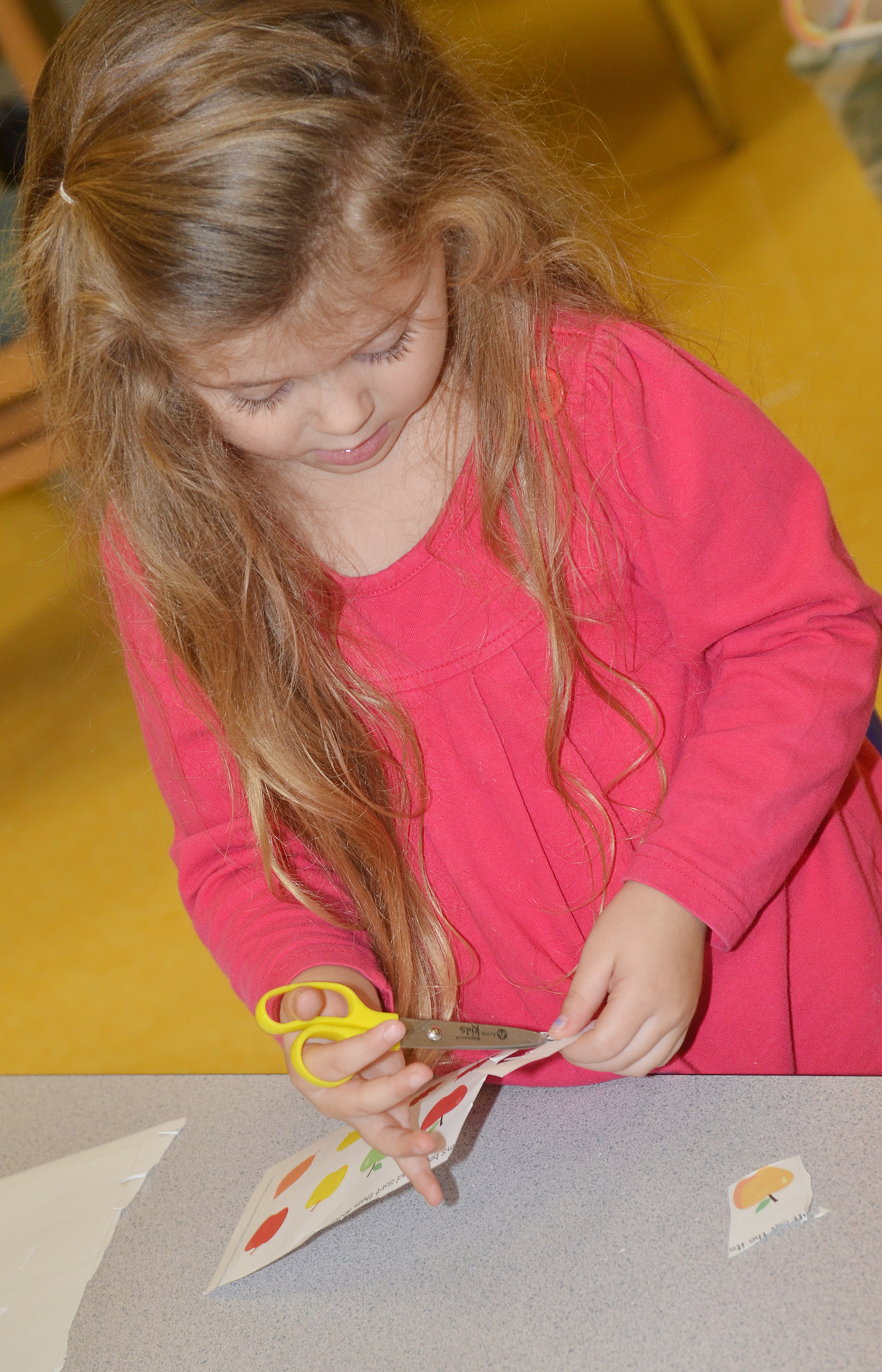 CES preschool student Mila Moss cuts out apples to sort by color.