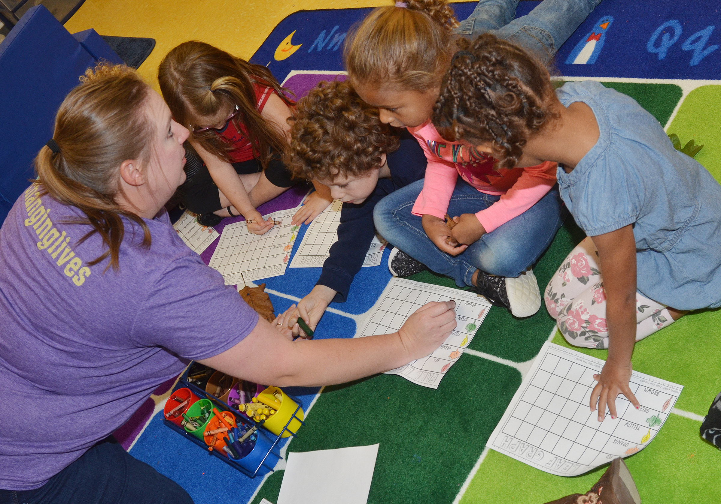 CES preschool teacher Julie Shelton and her students sort their leaves by color.