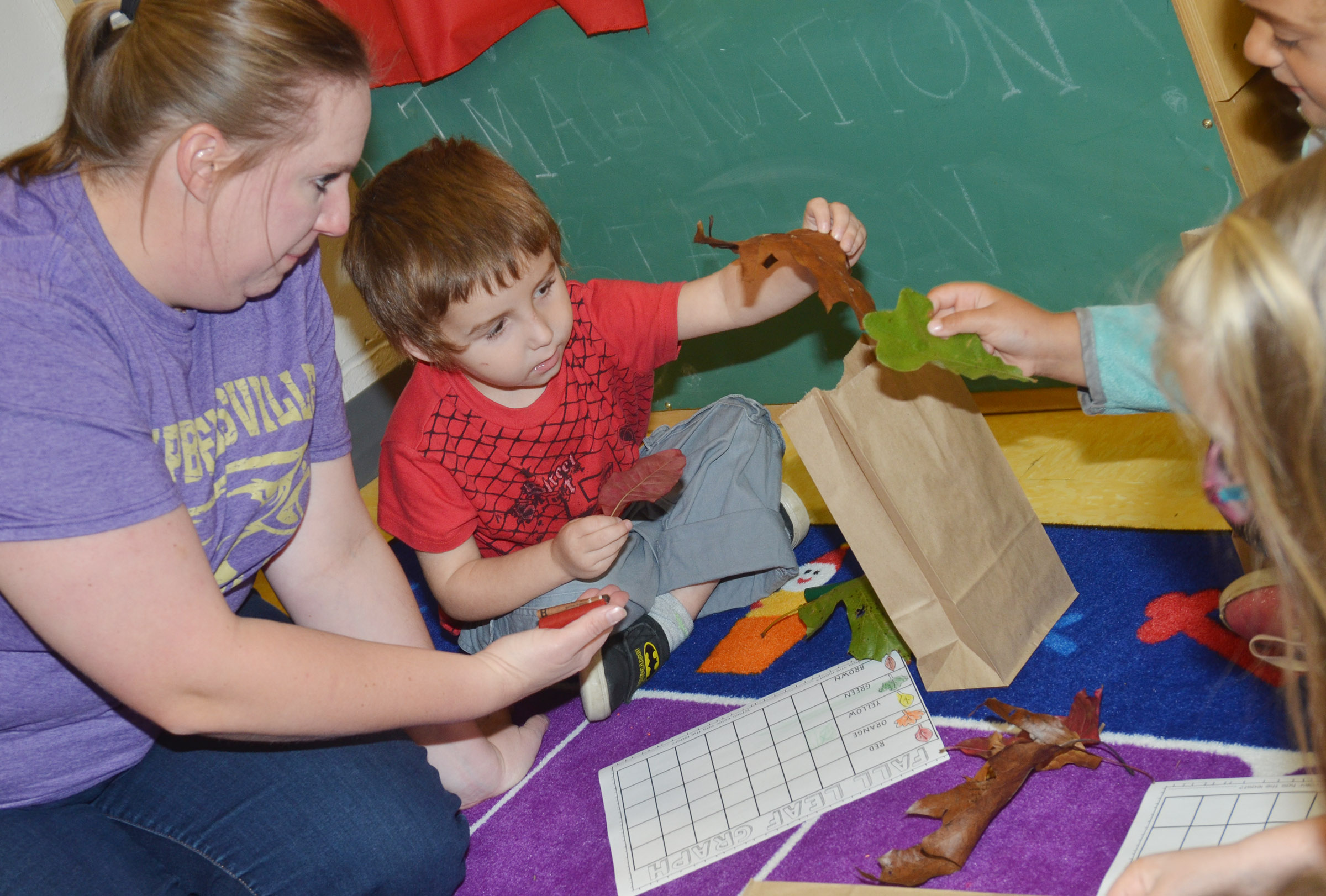 CES preschool teacher Julie Shelton and Noelan McMahan look at their leaves to see their colors.