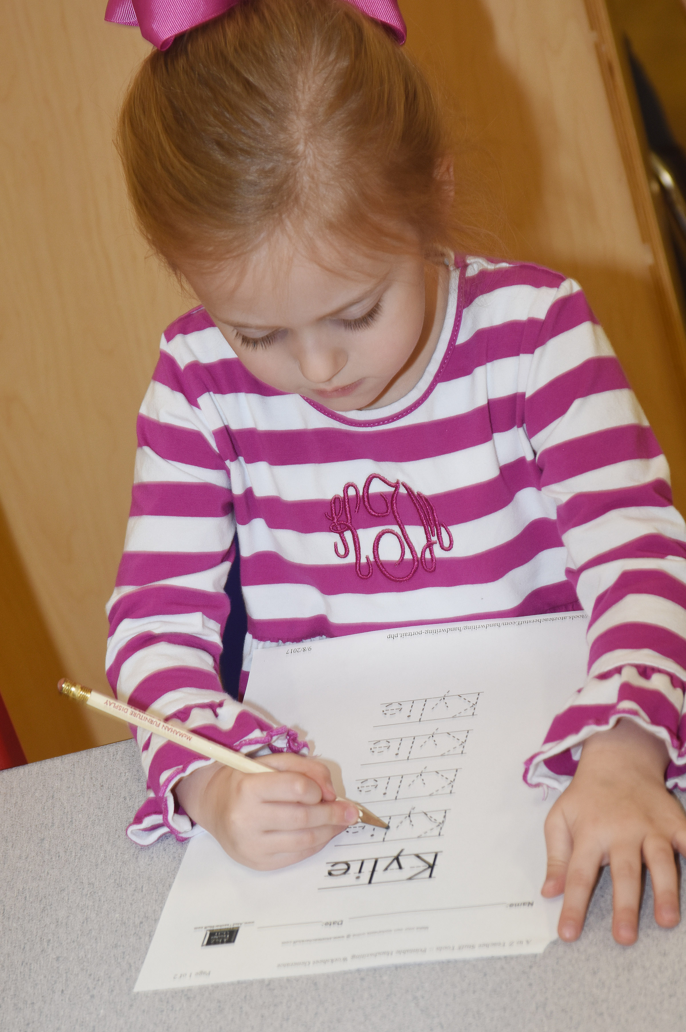 CES preschool student Kylie Thompson writes her name.