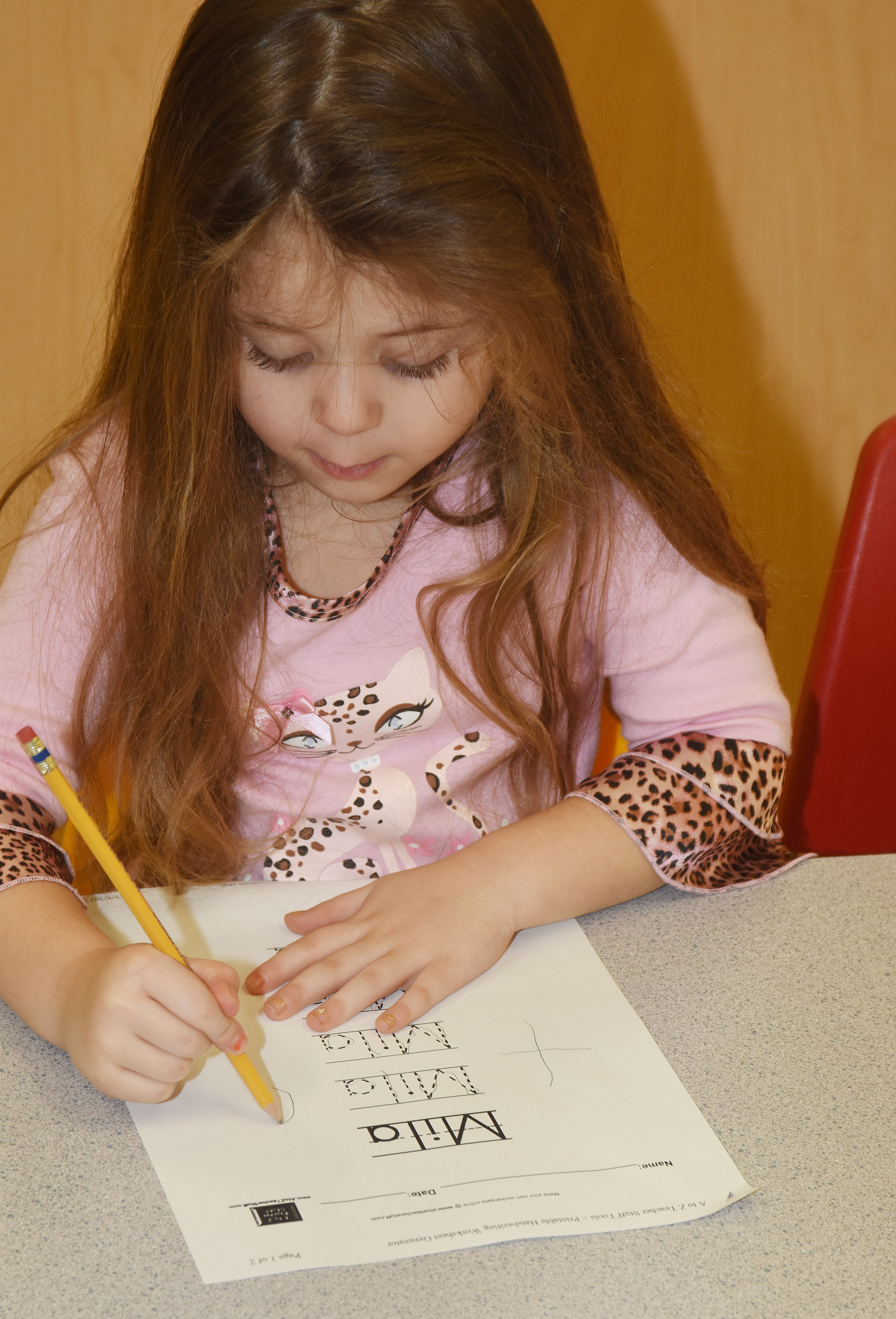 CES preschool student Mila Moss writes her name.