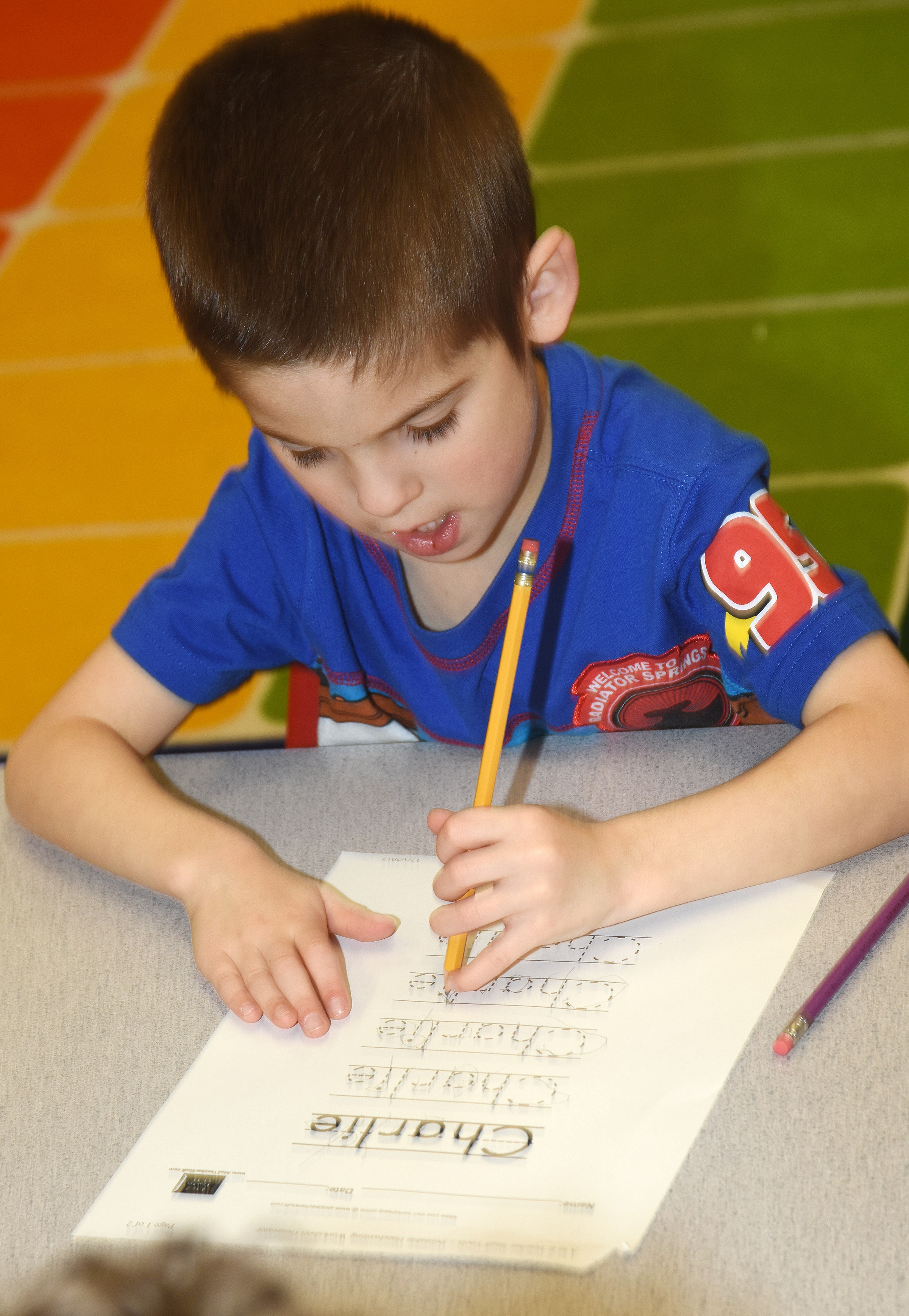 CES preschool student Charlie Woodbury writes his name.